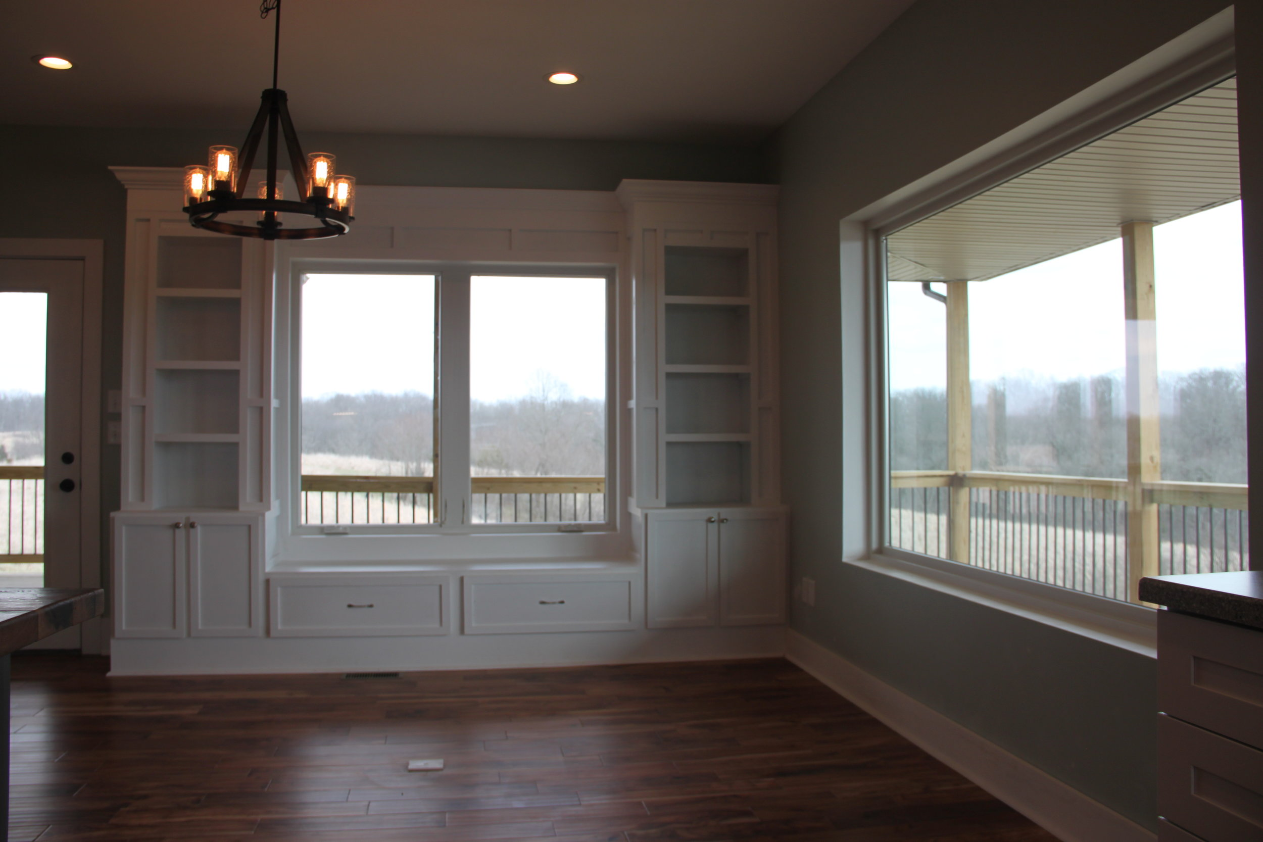 The dining room features a built in bookcase with a bench seat, and grand windows for the ultimate view while dining.