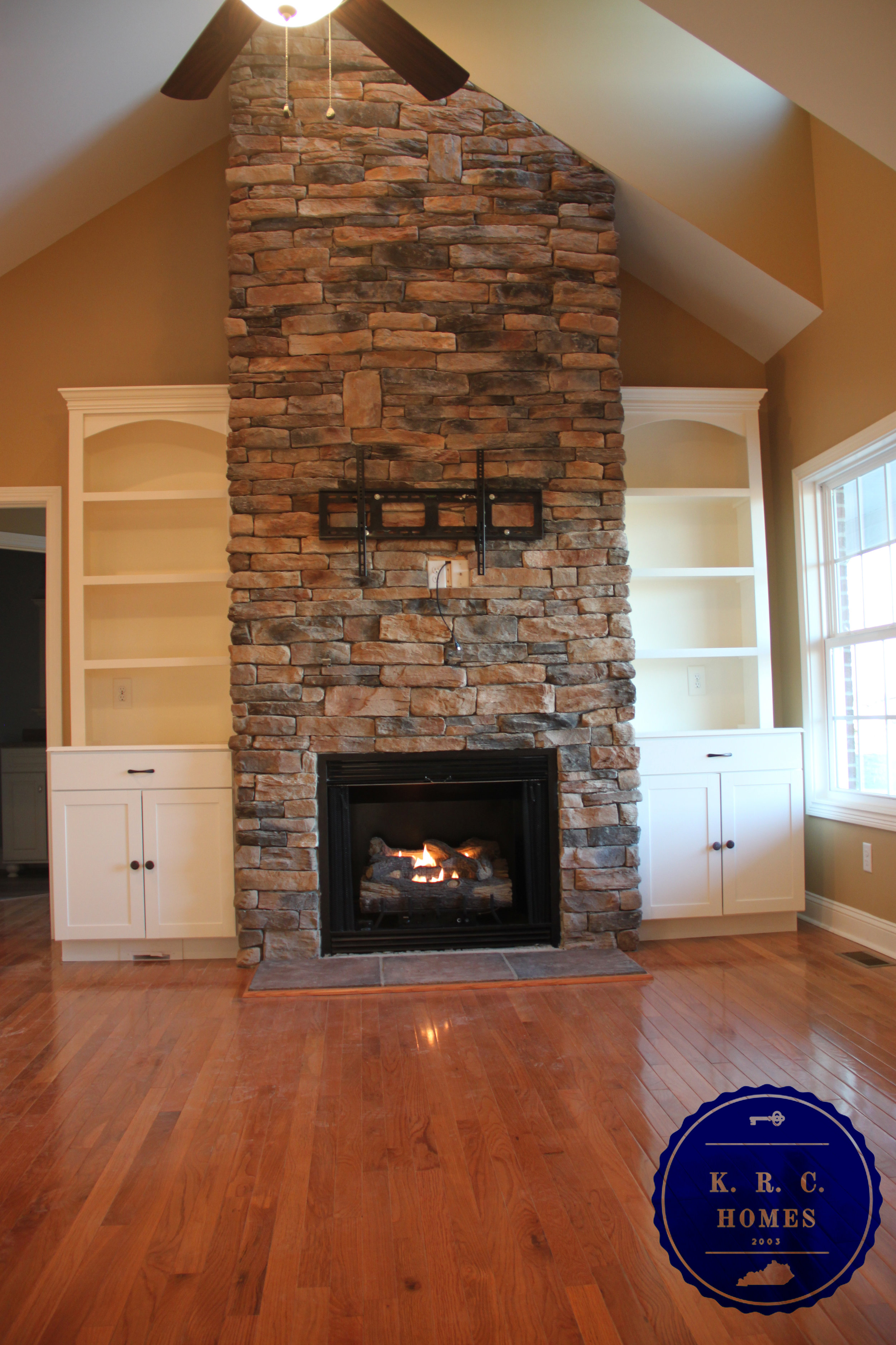 Stone fireplace with built-in bookshelves and vaulted ceilings in the family room