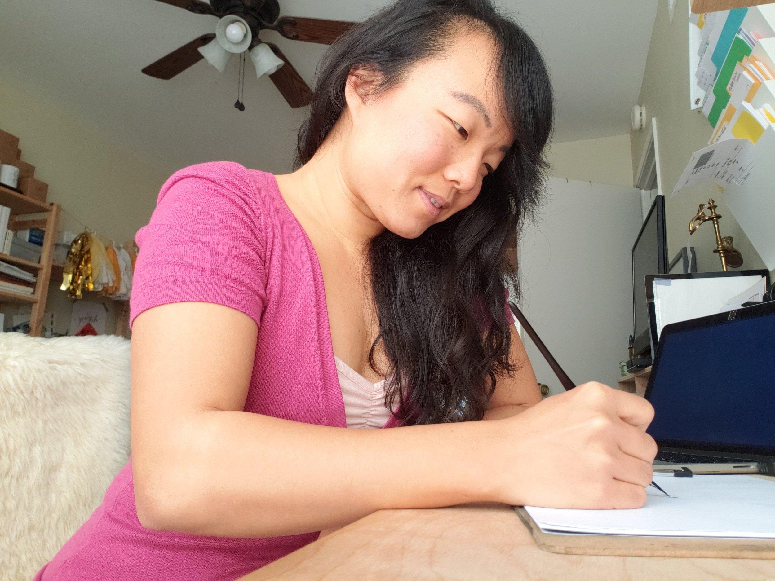 Calligrapher writing at her desk.jpeg