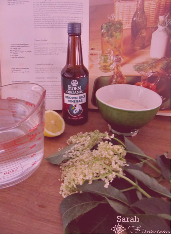 image: recipe book at the back with a vintage look, a measuring jug in front with a lemon, a bottle of rive vinegar, an elderflower and a green bowl with sugar in it next to.