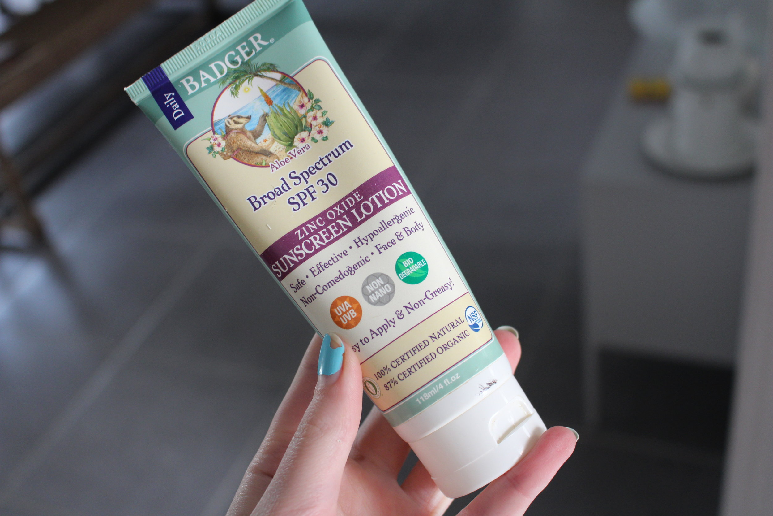 Image: my hand holding my tube of badger sunscreen lotion