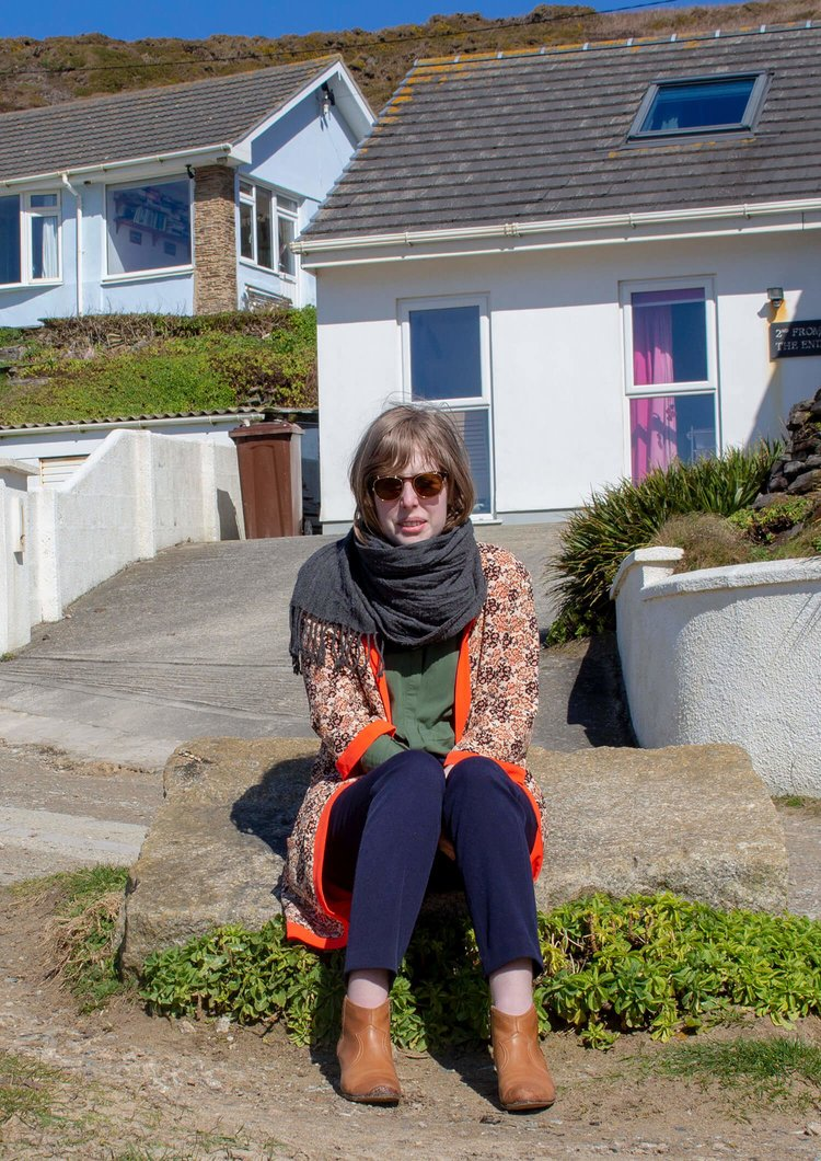 picture of me: I'm sitting on a rock by the beach in front of a beachy bungalow. I'm wearing a light long coat with light orange flowers and a dark orange trim. A grey big scarf, dark green shirt, blue dress pants and camel colored leather ankle boots