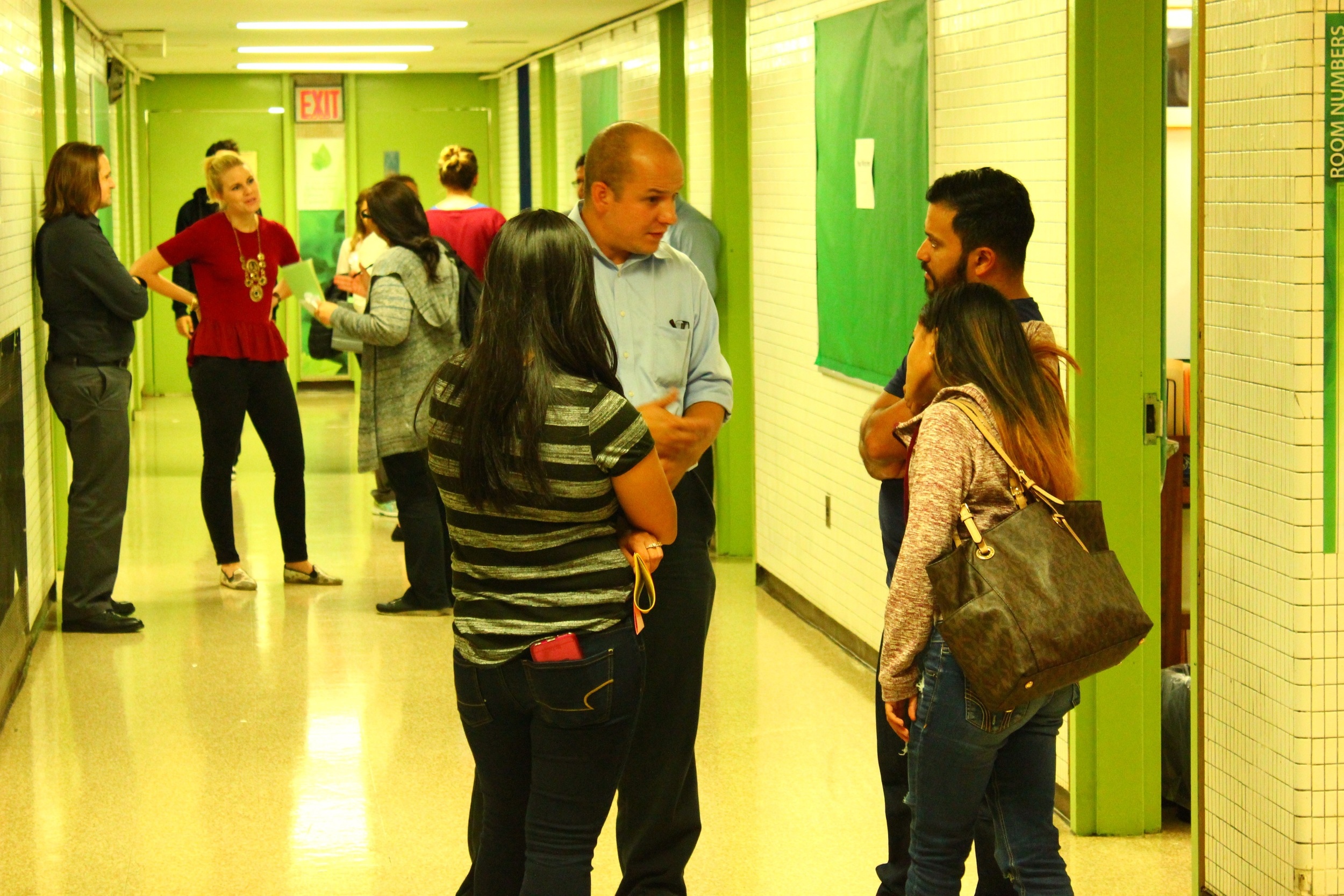 Parents speaking with Global History teacher, Marco Arango, at the Fall Curriculum Night, featuring food, fun, and an introduction to the incredible work of students at UAGC