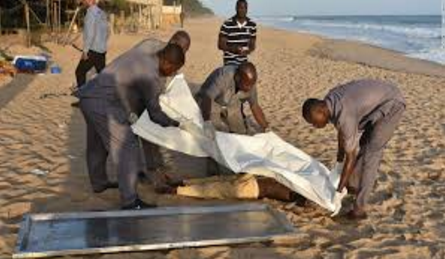 This picture is also another dead male body on the Beach of Ivory Coast and a group of males covering it up (Dailymail.co.uk)
