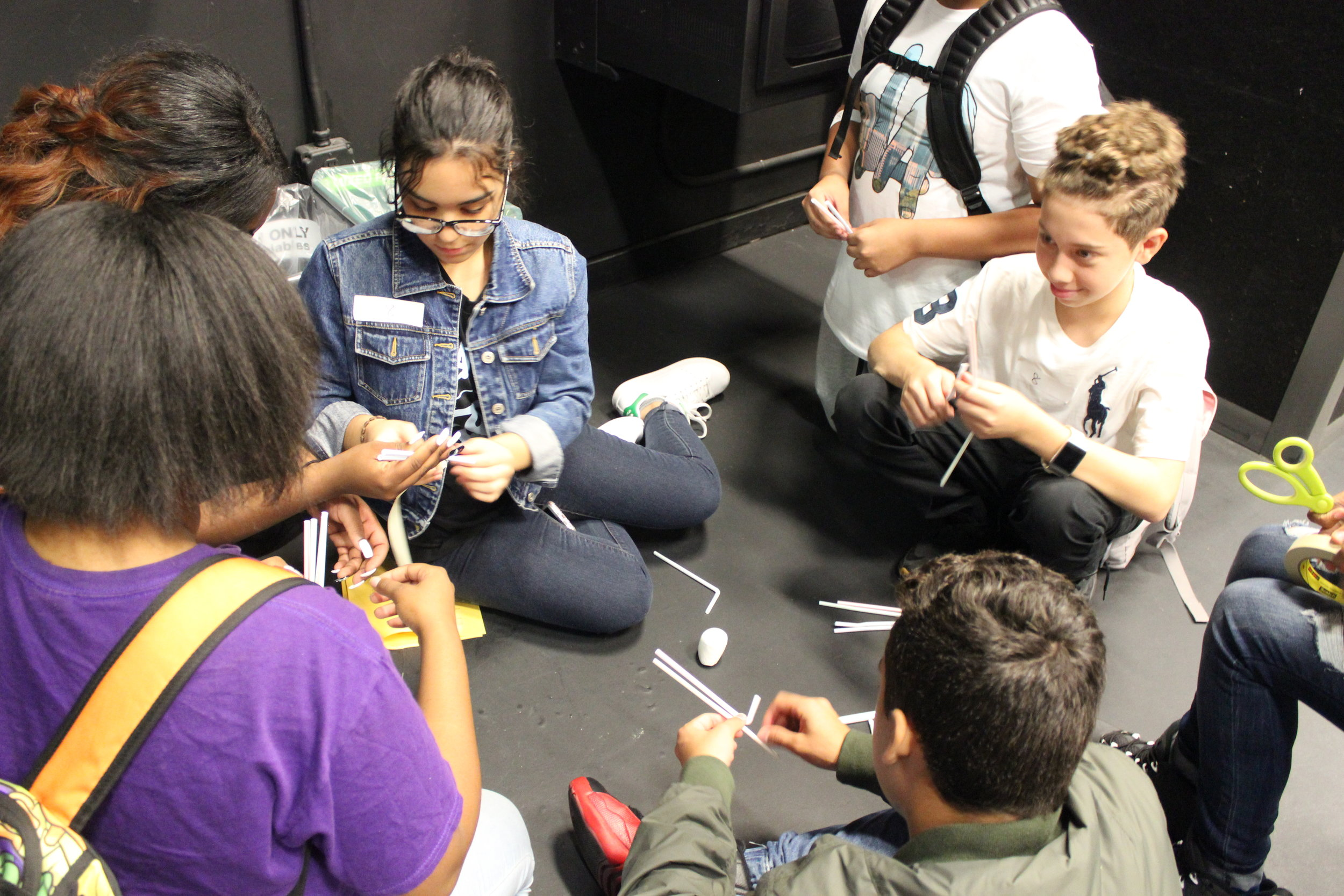 Alumni Fradaliza Valdez, current Queens College student, works with a silent group of new UAGC students