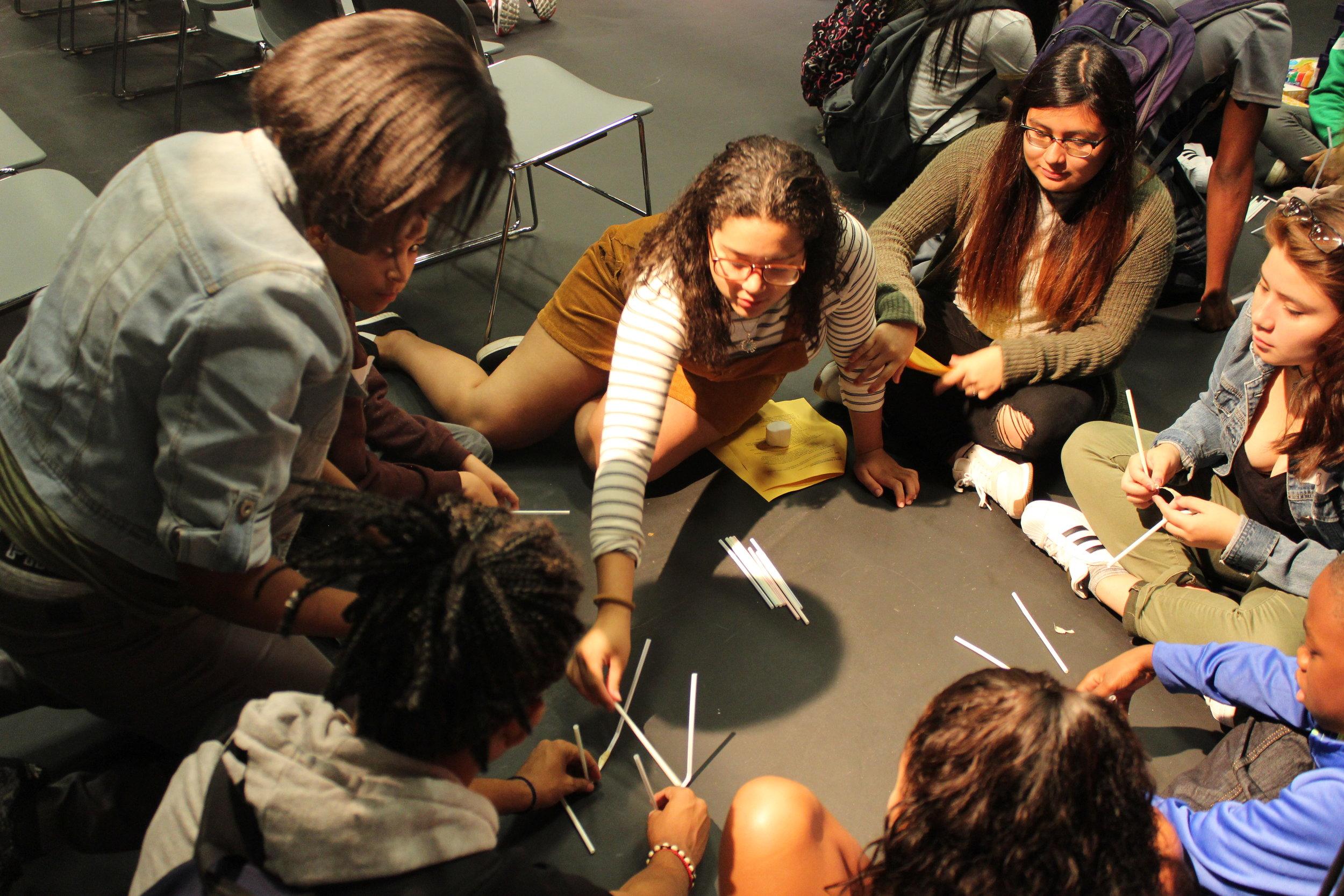 Alumni Jailine Estrella, center, current NYU freshman, attempts to spread ideas without speaking