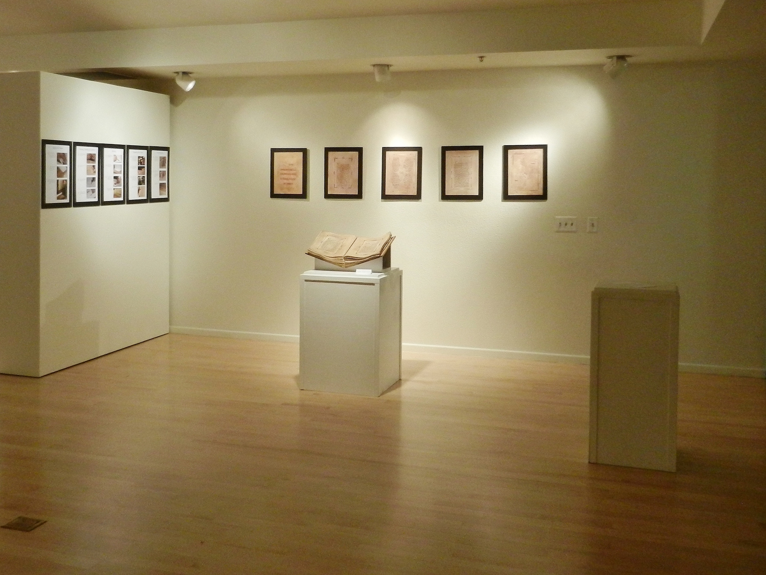 Friesen Galleries,  A Song of Glory , 2012. The pages mounted beside the manuscript depict the creative process that went into this project; the pages mounted behind are scans of folios throughout the book (provided as viewers were not permitted to touch artworks on display).
