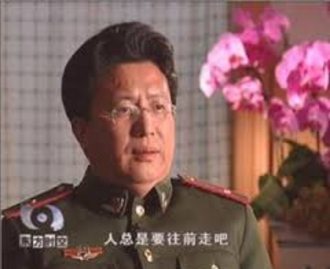 """Dr. Shen Zhongyang is interviewed on Chinese television in his paramilitary uniform. The subtitle says """"humankind will always make progress."""""""