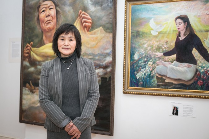 Artist Li Jinyu, with her artwork at the exhibition by AAFOH (Artists Against Forced Organ Harvesting) in New York on May 10, 2016. The exhibition features artwork about human rights abuse in China as well as Falun Gong practitioners speaking out against injustice in China. (Benjamin Chasteen/Epoch Times)