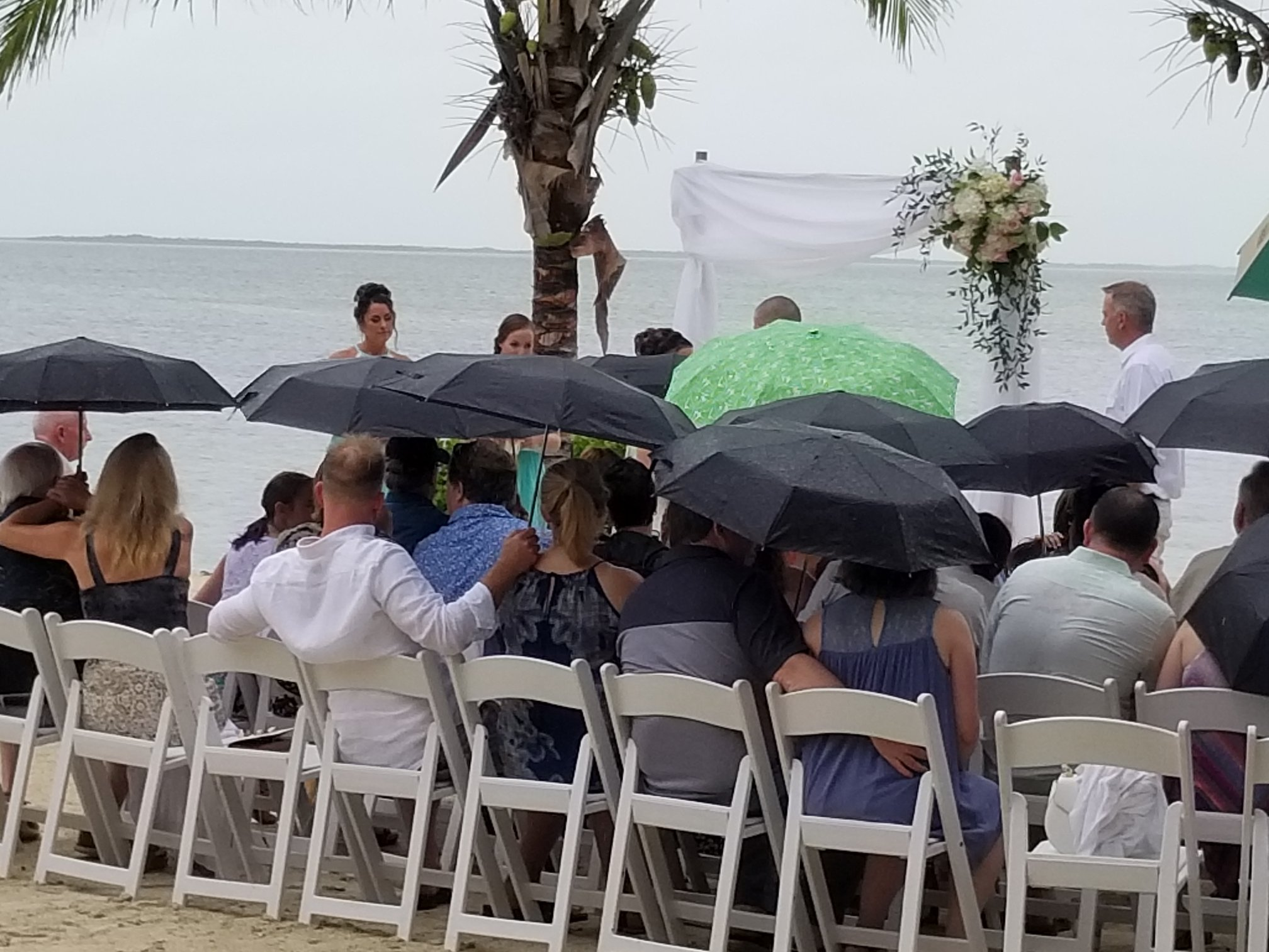 Any good team of vendors can get the job done when everything is going great, but the true mark of a great team is pulling off the perfect wedding under adverse conditions.  When we all arrived at yesterdays reception, it was pouring rain. Buckets of rain is more like it. Our bride and groom had planned for this beach side wedding in the beautiful Florida Keys with 70 of her close family and friends, only to be greeted by a Sub Tropical Storm off the west coast of Florida producing moderate winds and heavy rain over the entire Keys chain..  Of course the bride was somewhat anxious about this turn of events. After all, she had been planning this wedding for almost a year.  We all put on our happy faces and told her we would make this perfect for her and we didn't disappoint. With live radar apps on our phone, we kept track of the rains every moment. Between the planner, caterer, photographer, and of course yours truly, we plotted the storm and figured out when would be the best time to do things based on breaks in the weather. The entire day was moved up by one hour which is easy when you're having a destination wedding and you know where everyone is staying to get word to them. Once we had all the guests there, we knew we had a window of 30 minutes during a break in the weather. The planners and venue staff jumped into action, had the chairs wiped dry, lined up the wedding party, and got that ceremony started. It sprinkled a little bit but the ceremony was perfect.  During cocktail hour we decided we had enough time to do the grand introductions outside along with our spotlight dances. The bride was beaming with happiness.  Once the dances were complete, we invited all of the guests into the dinner tent. It started to rain again on and off during dinner and dancing. The catering staff had to go back and forth between the main tent and their catering facilities and most of them were drenched but not one had any complaints. They had one mission, feed the guests, keep 