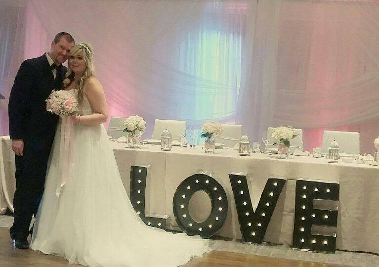 Bride & Groom in front of LOVE sign | Evelyn's Decorating
