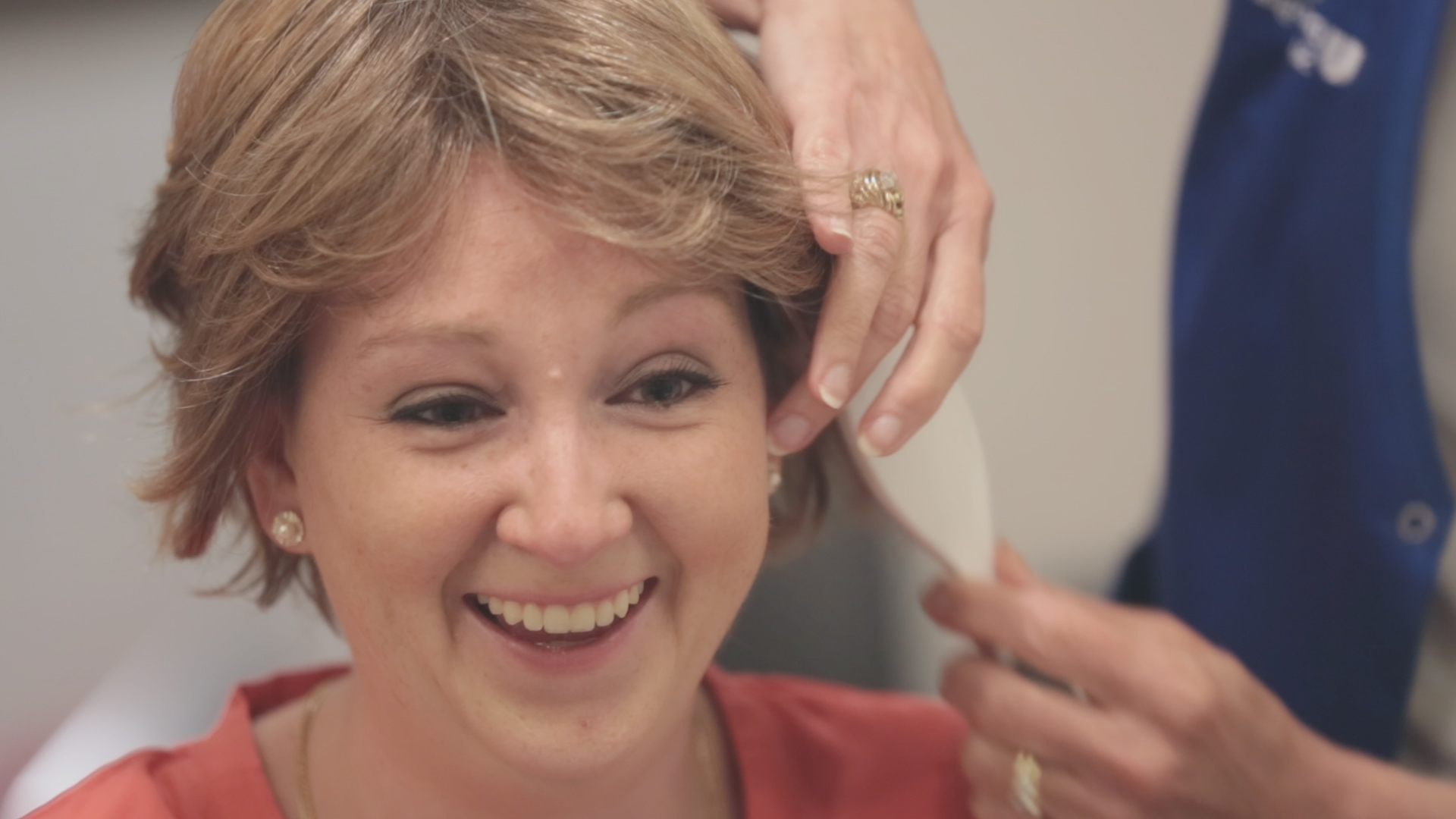 Breast cancer patient Lori Elliott smiles while trying wig on at Duke Cancer Institute