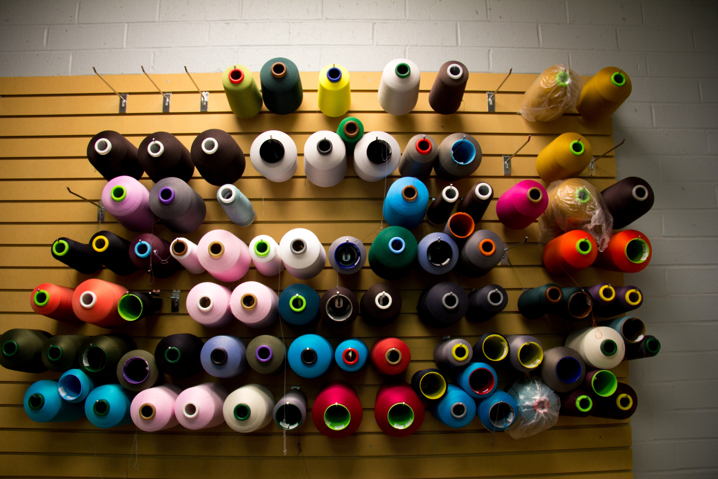 Colorful spools of fabric hanging on wall