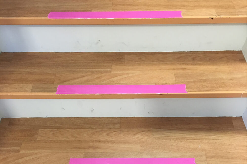 Mark tripping hazards such as the edge of a step with bright colour tape