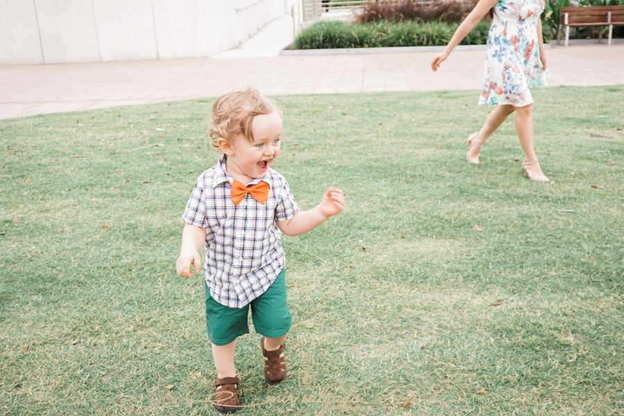 baby-boy-giggles, tiny-joy, little-feet-running, orange-bowtie, grassy-field