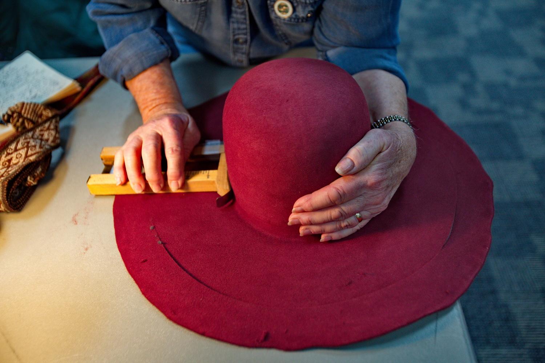 Trimming at the Hatmaking Workshop. Photo by Charlie Ekburg.