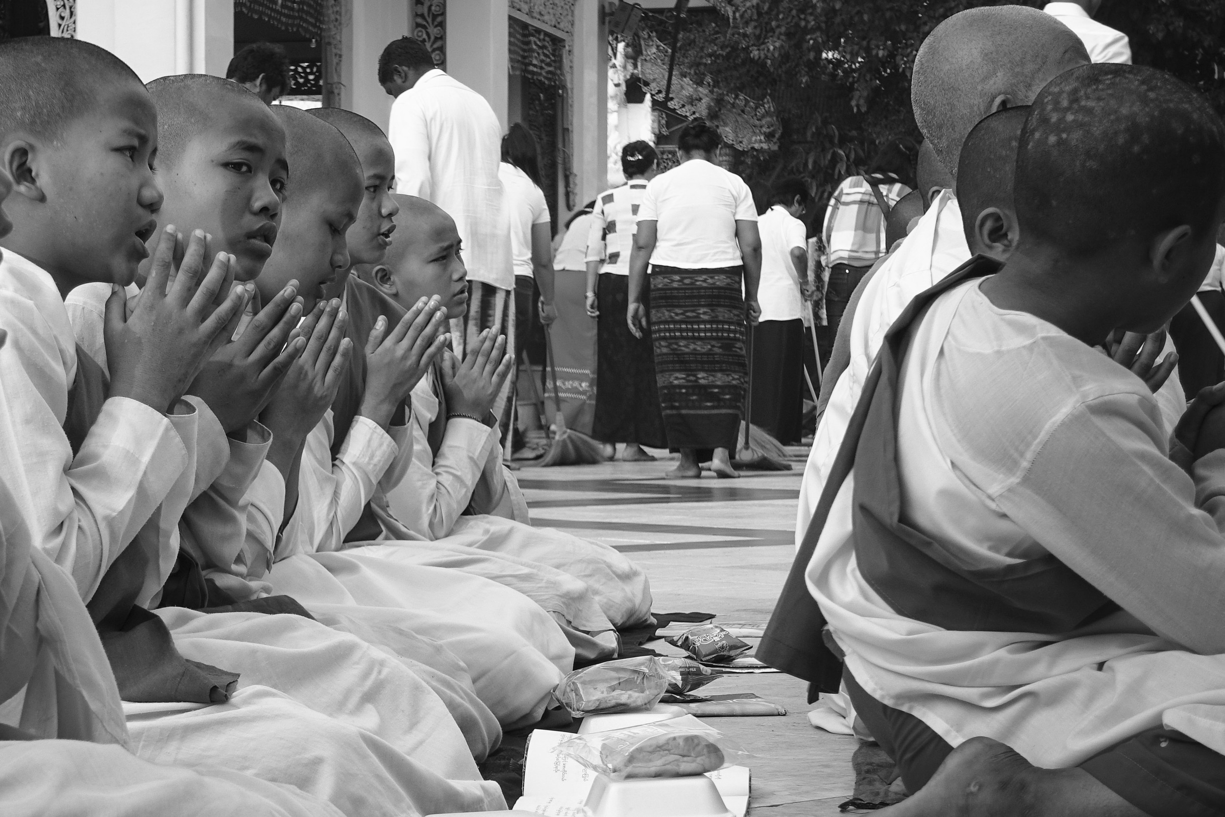 Young monks move around the central pagoda structure, singing hymns and collecting alms.