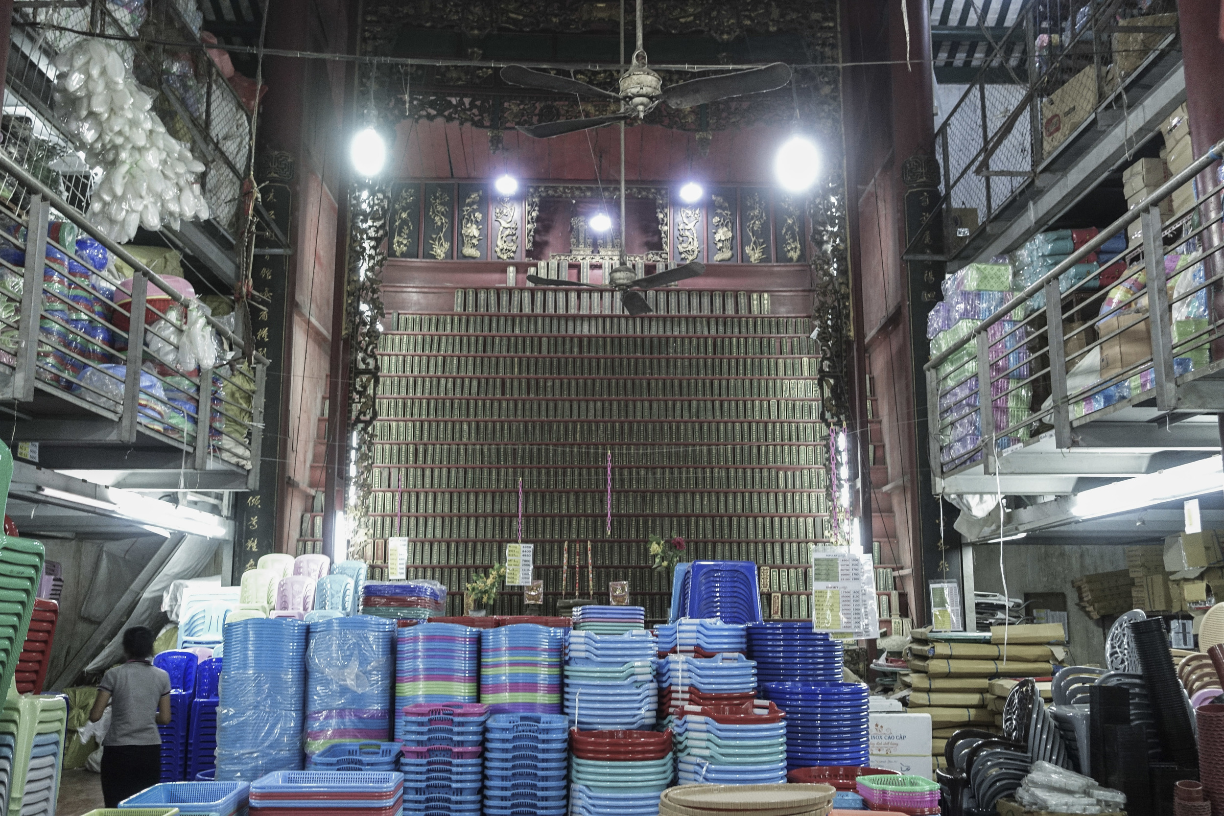 A 'donation' wall for blessings sits at the back of a plastic goods warehouse.