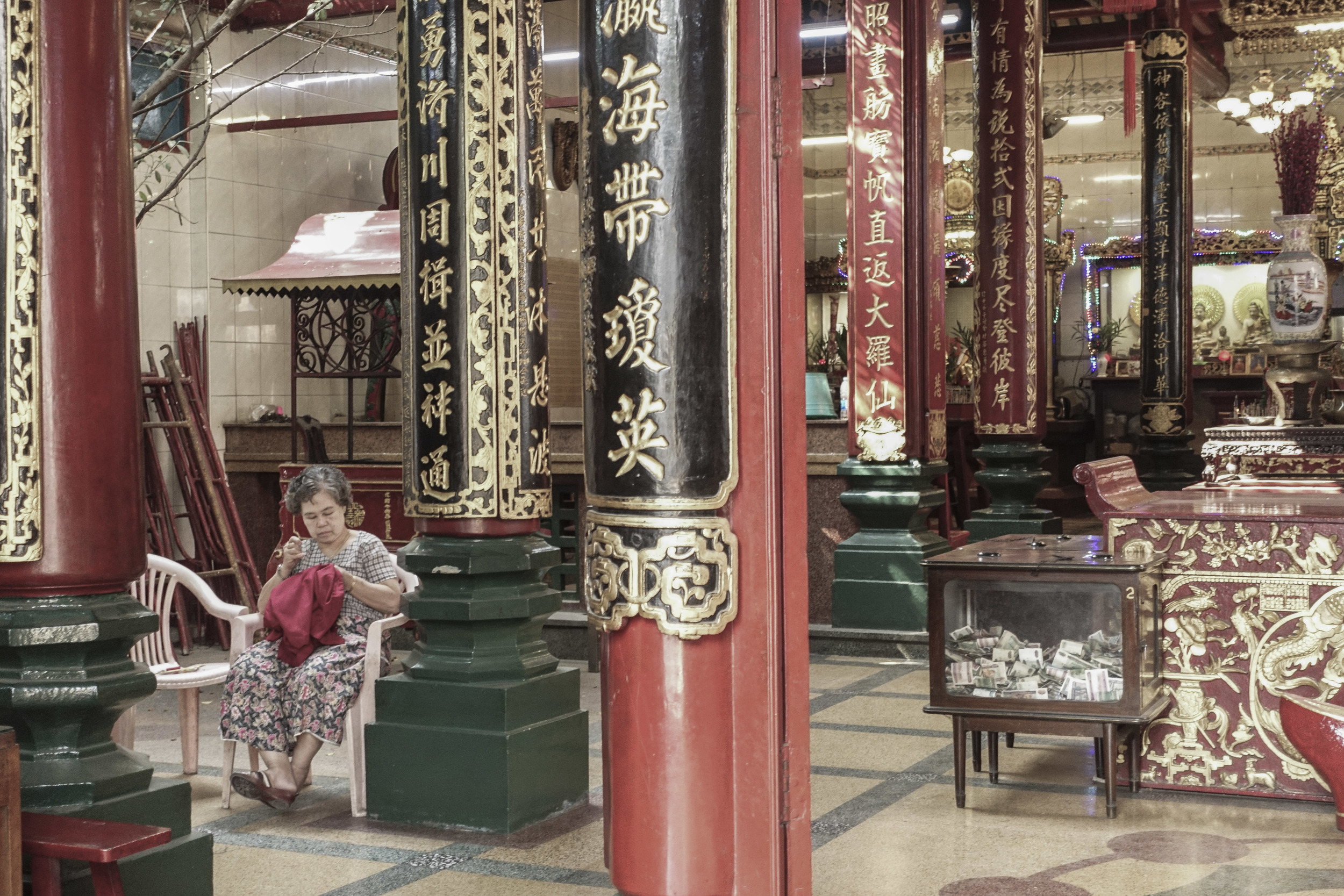 A woman finds a quiet place to knit at the Cantonese Guan Yin Temple beside 20th Street.