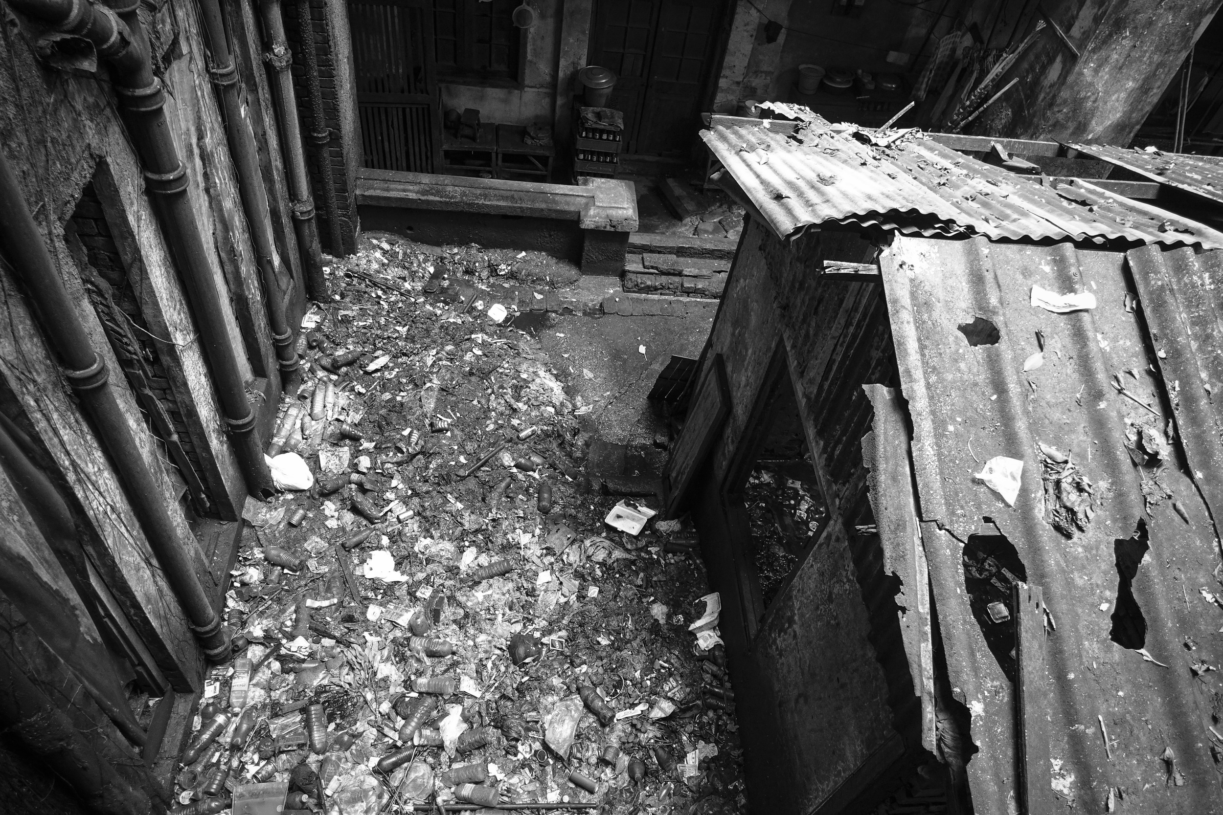 The building is possibly too far gone to be restored. A broken-down shack occupies the interior courtyard, surrounded by a moat of trash.