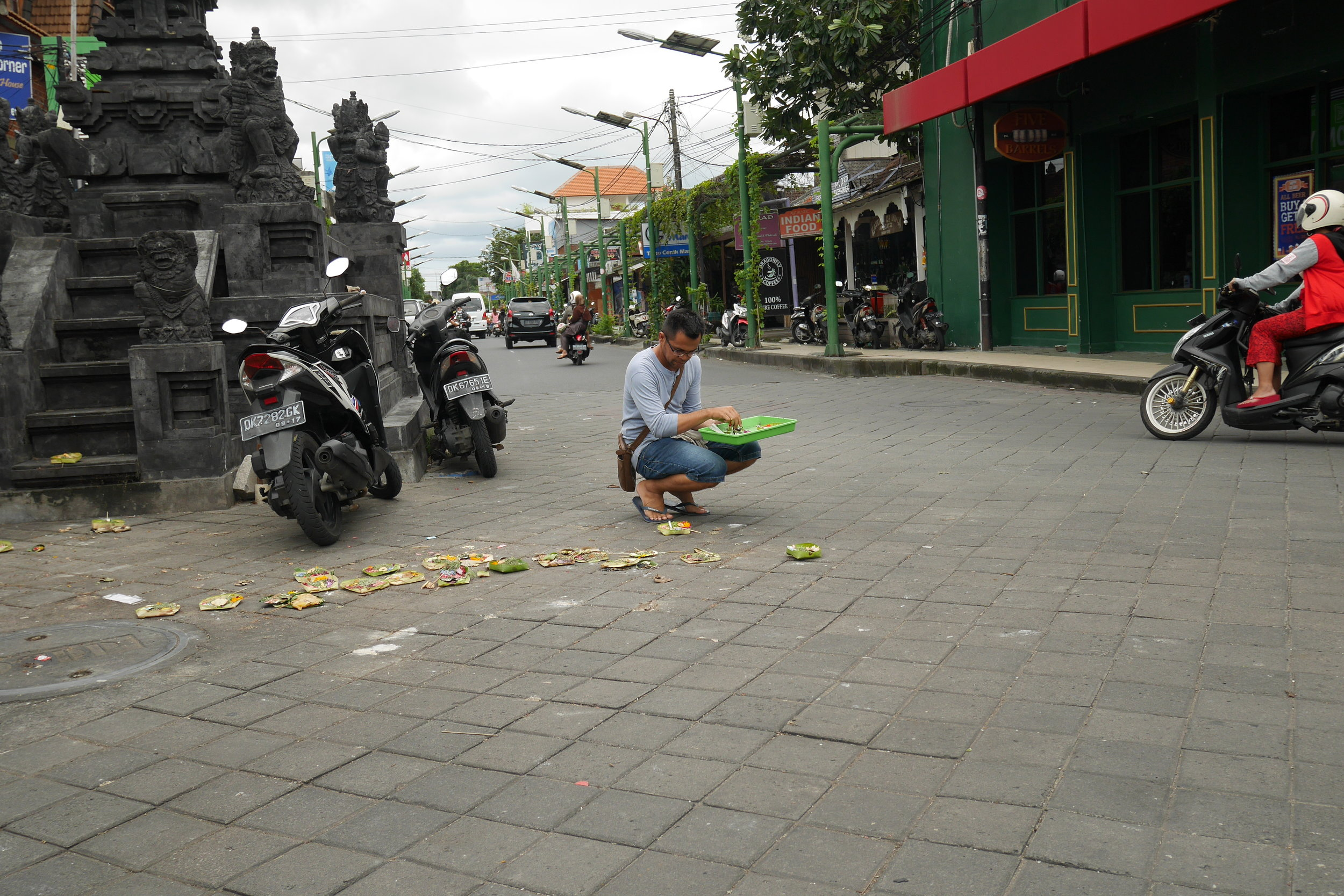 A man offers prayers on the road, oblivious to the bustling incoming traffic.