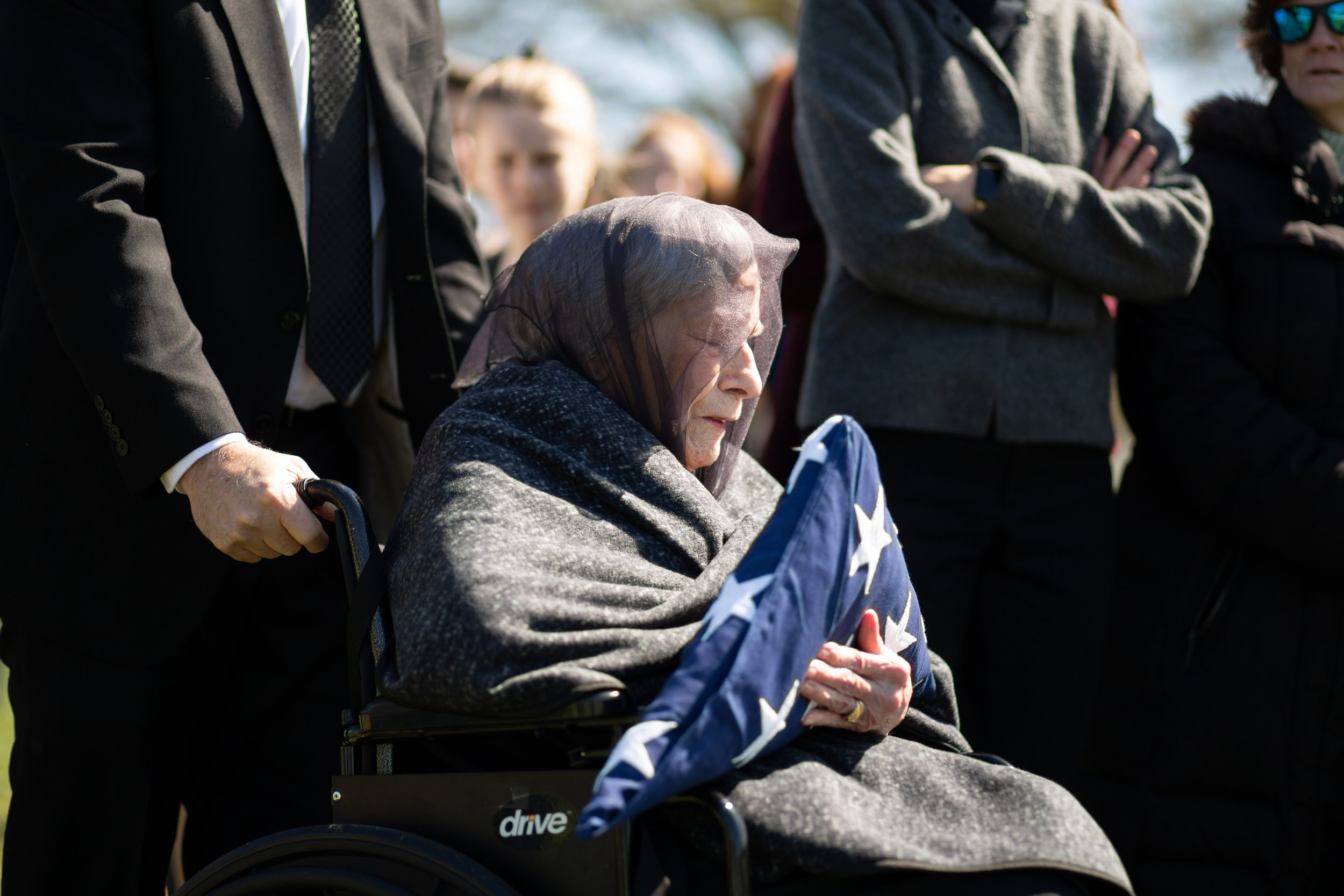 WASHINGTON D.C., April 21, 2018-- A widow clutches the flag as she gives her last goodbyes to a dearly missed husband.  Photo by Taylor Mickal