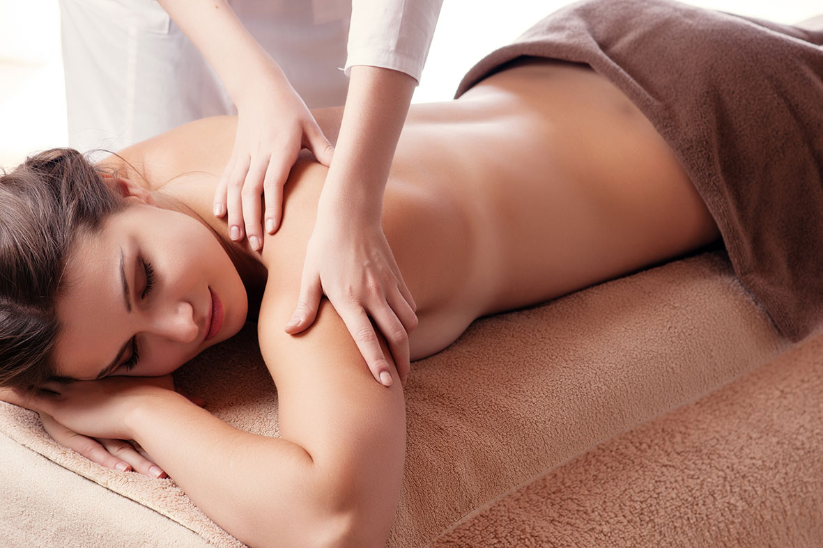 woman lying on front with hands massaging