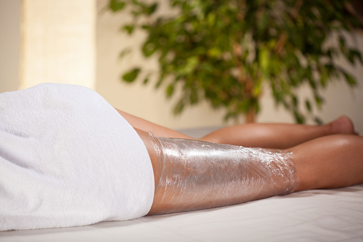 woman with white towel and one leg wrapped in cling film