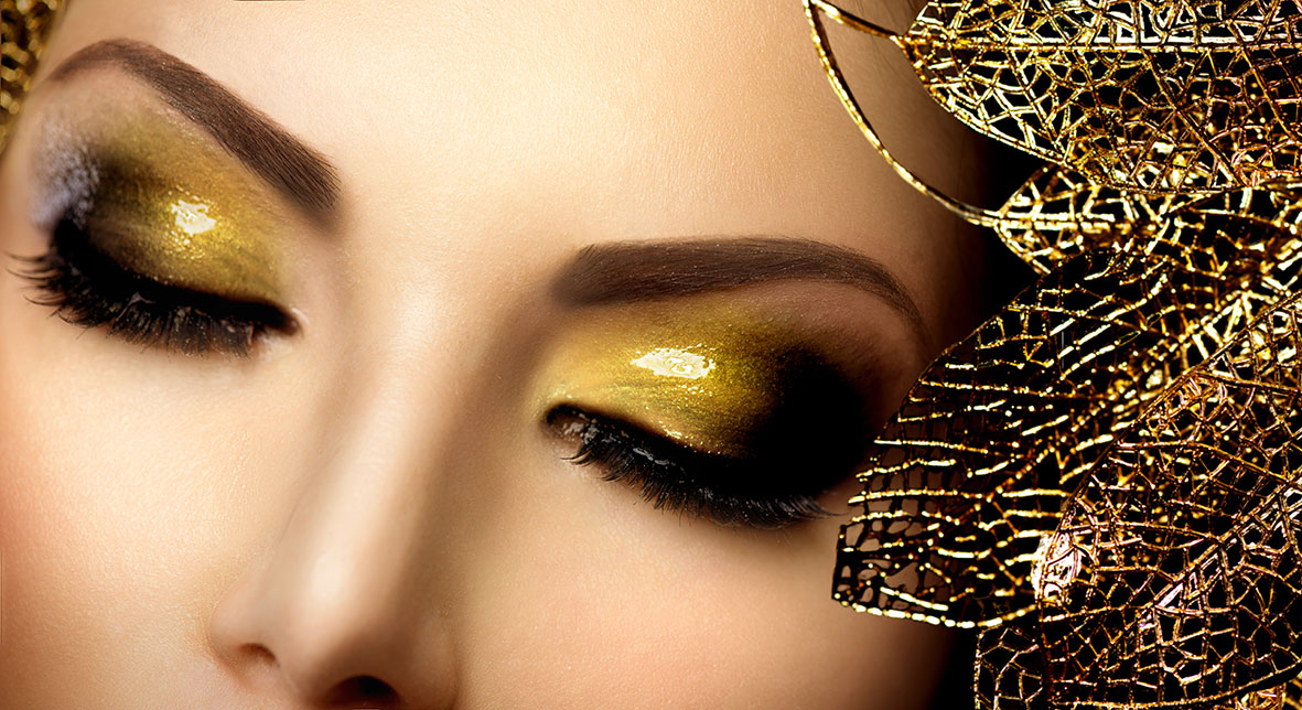 glossy golden eye shadow on woman with golden leaf