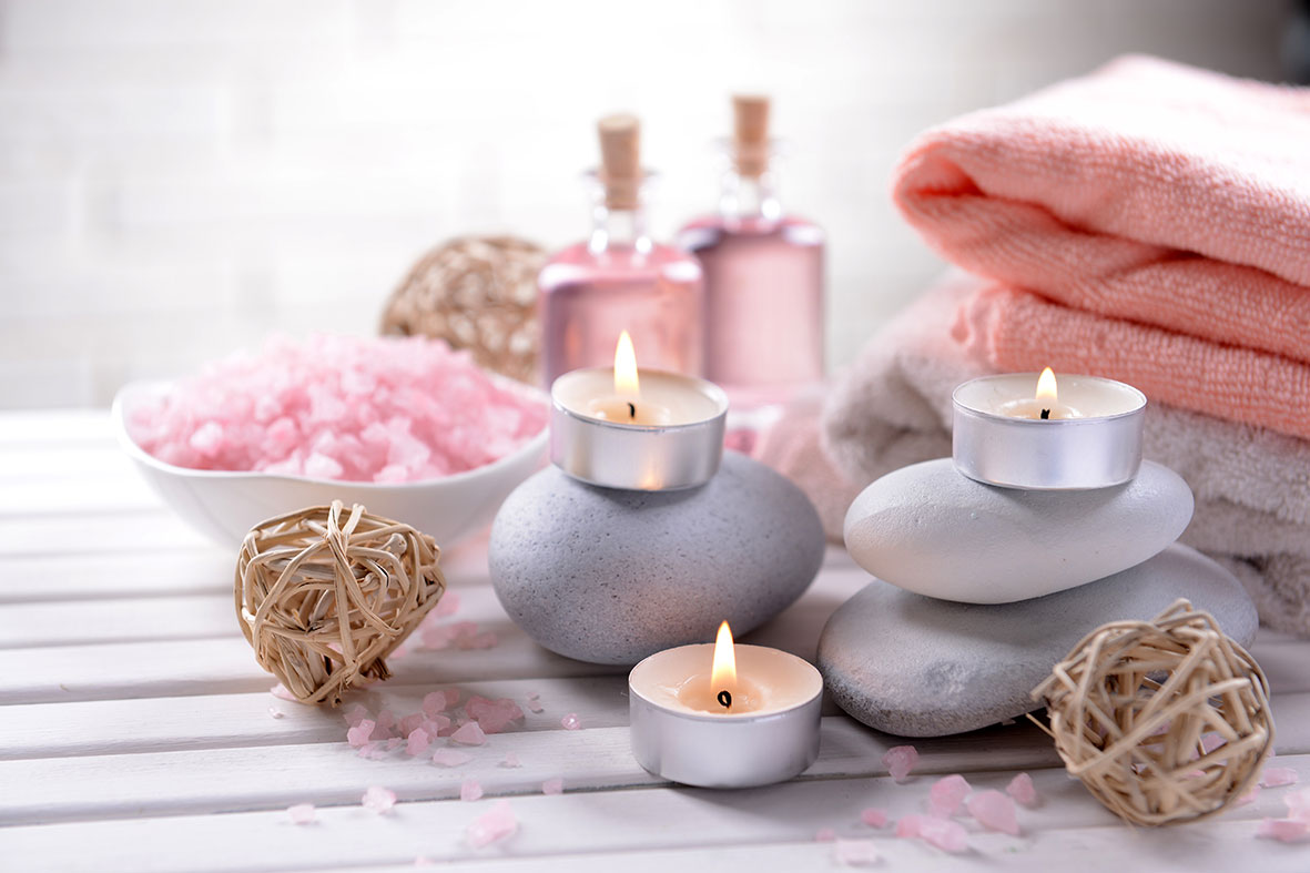 tea light candles on pebbles with pink towels