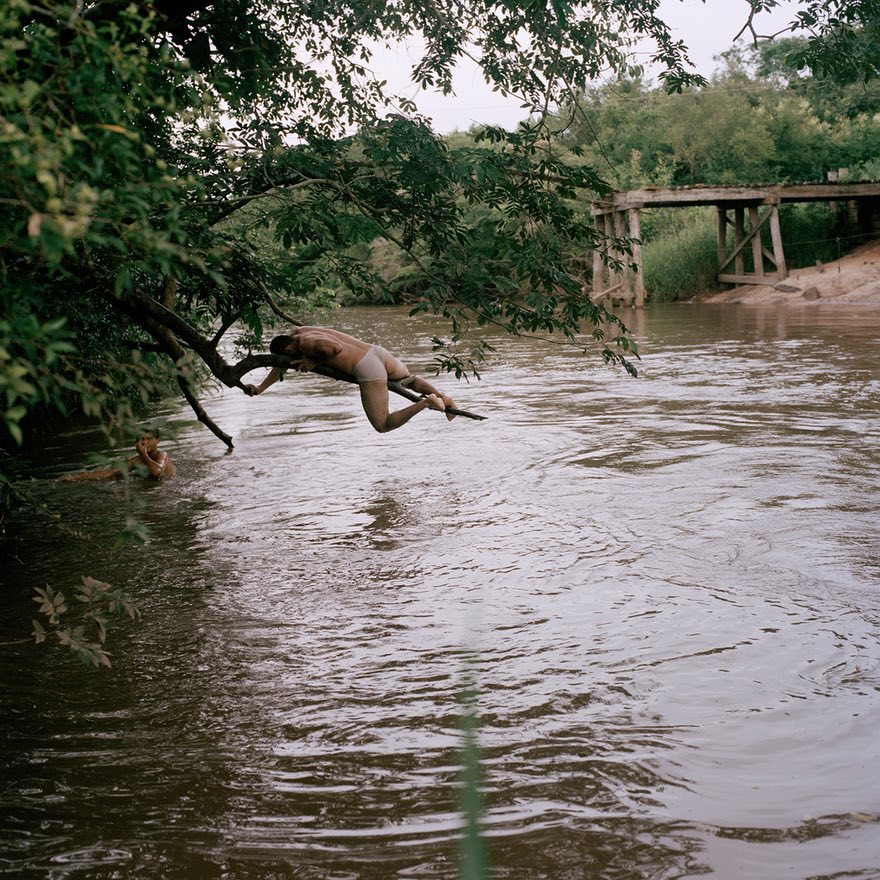 - 'A group of teenagers swim in a river near the Tava Jopoy community. Neighbours claim it's severely polluted due to pesticides used in the nearby large estate plantations, with whom they are in an ongoing conflict. There are regular protests against the fumigations'