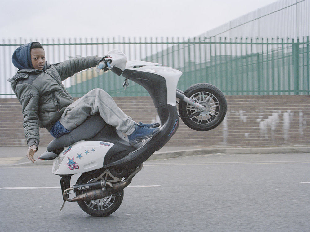 - LB Looney wheelies along an industrial estate road, NE London'There's seemingly a right of passage within the community that starts with kids on pushbikes spectating and emulating their elders by doing pedal wheelies, then once they come of age they will put an L plate on a scooter, and then finally graduate to the more powerful motorbikes'