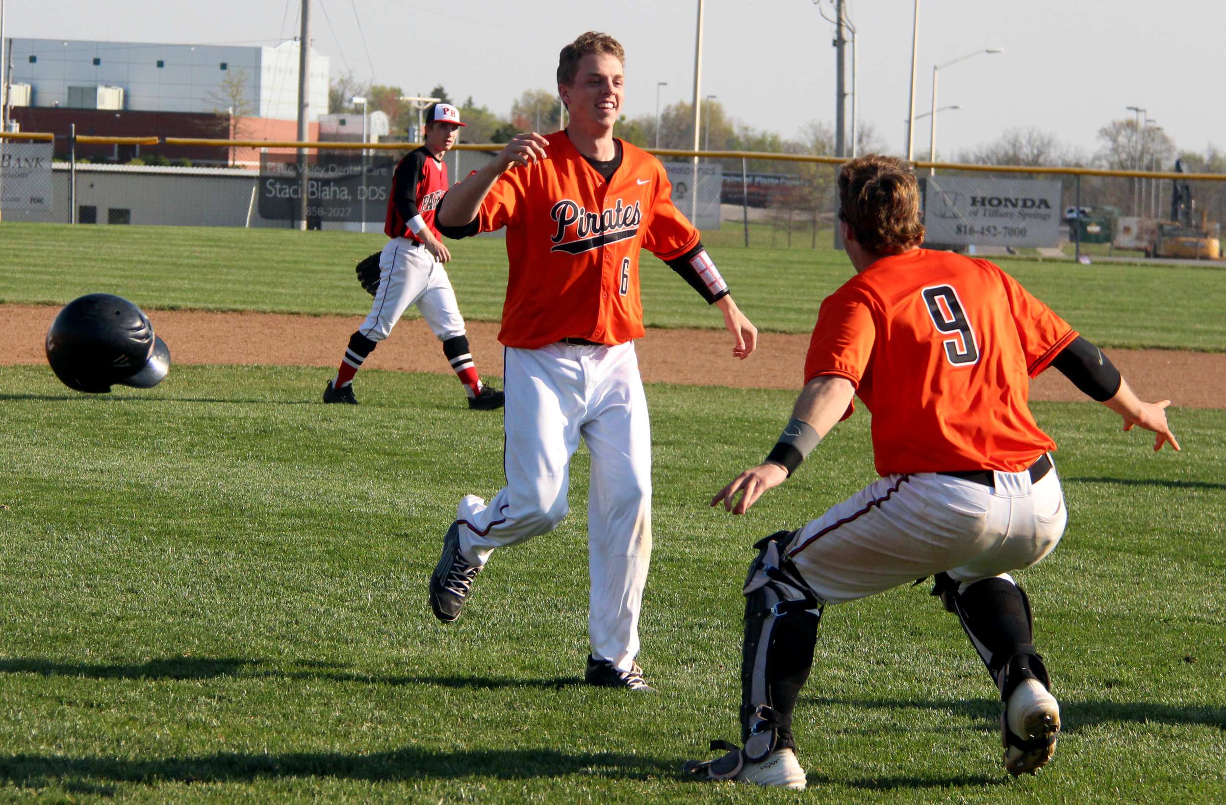 ROSS MARTIN/Citizen photo Platte County senior Jerod Thomas (6) tosses aside his helmet and prepares to jump into the arms of junior catcher Justin Mitchell following a win over Park Hill on Wednesday, April 13 at Platte County High School.