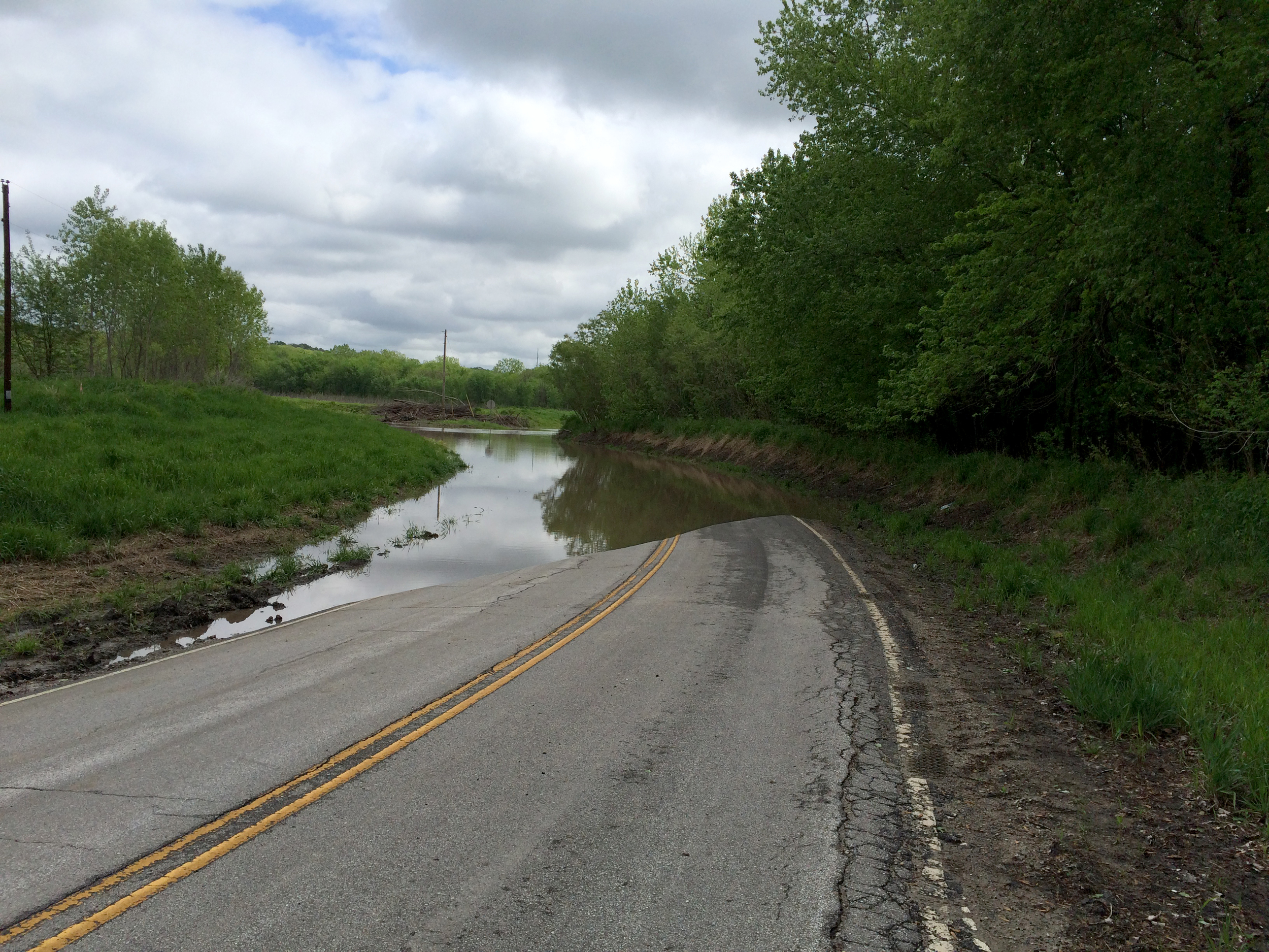 ROSS MARTIN/Citizen photo Water covers the road around a bend of Highway E east of Camden Point on Wednesday, April 27. Heavy rains throughout the week led to localized flooding in much of northwest Missouri.