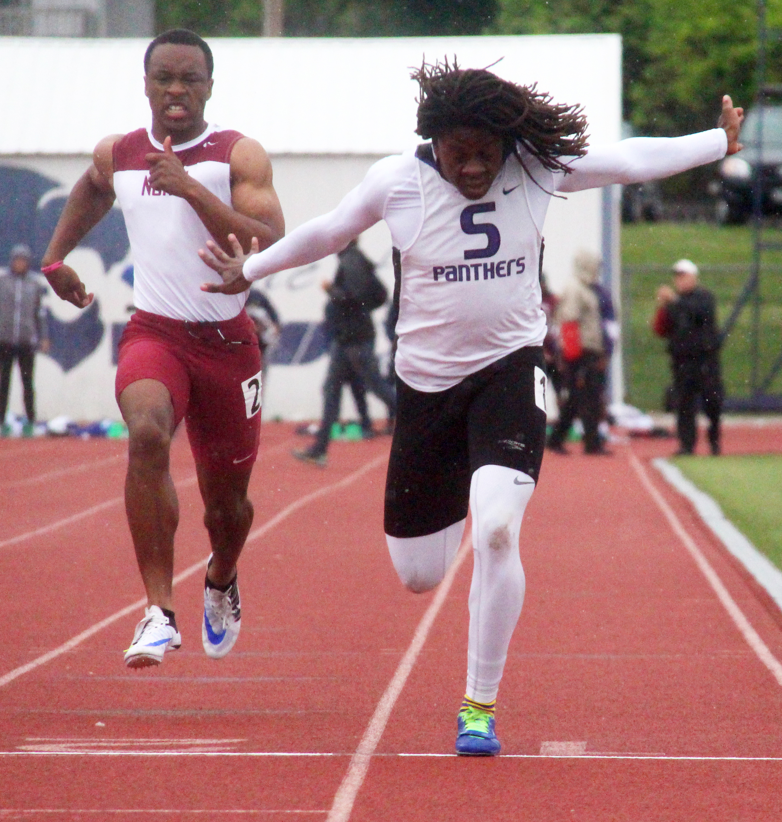 ROSS MARTIN/Citizen photo Park Hill South junior Nylo Clarke, right, lunges for the finish line in the 100-meter race Friday, April 29 in the Gary Parker Invitational at Blue Springs High School in Blue Springs, Mo. The meet was eventually canceled due to inclement weather.