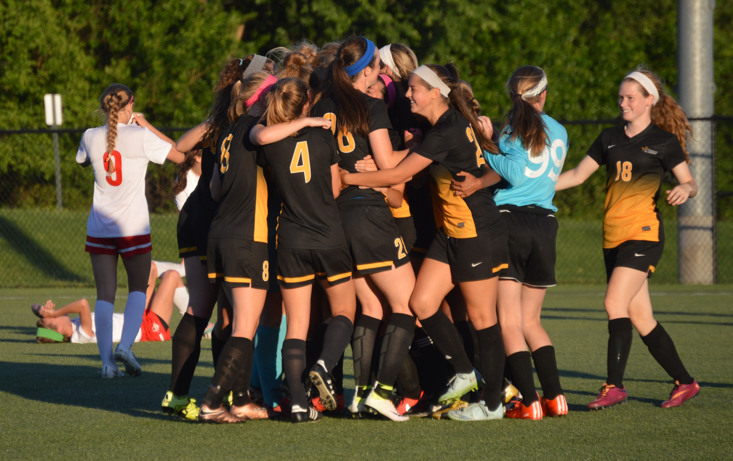 BRENT ROSENAUER/Citizen photo St. Teresa's Academy players celebrate a 2-0 victory in a Class 4 quarterfinal Saturday, May 28 at Park Hill District Soccer Complex in Riverside, Mo. Park Hill junior Jenna Winebrenner, back left, lays on the turf while senior midfielder Bella Catano covers her face with her jersey.