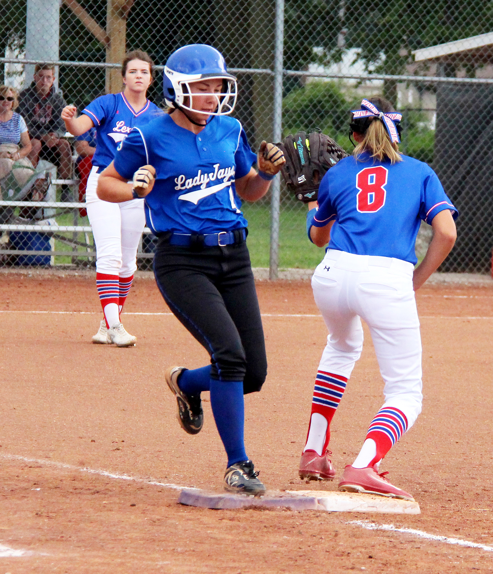 ROSS MARTIN/Citizen photo West Platte first baseman Rachel Heili, left, beats out an infield single during a North Platte Invitational game against Lexington on Saturday, Aug. 20 at Dean Park in Dearborn, Mo.