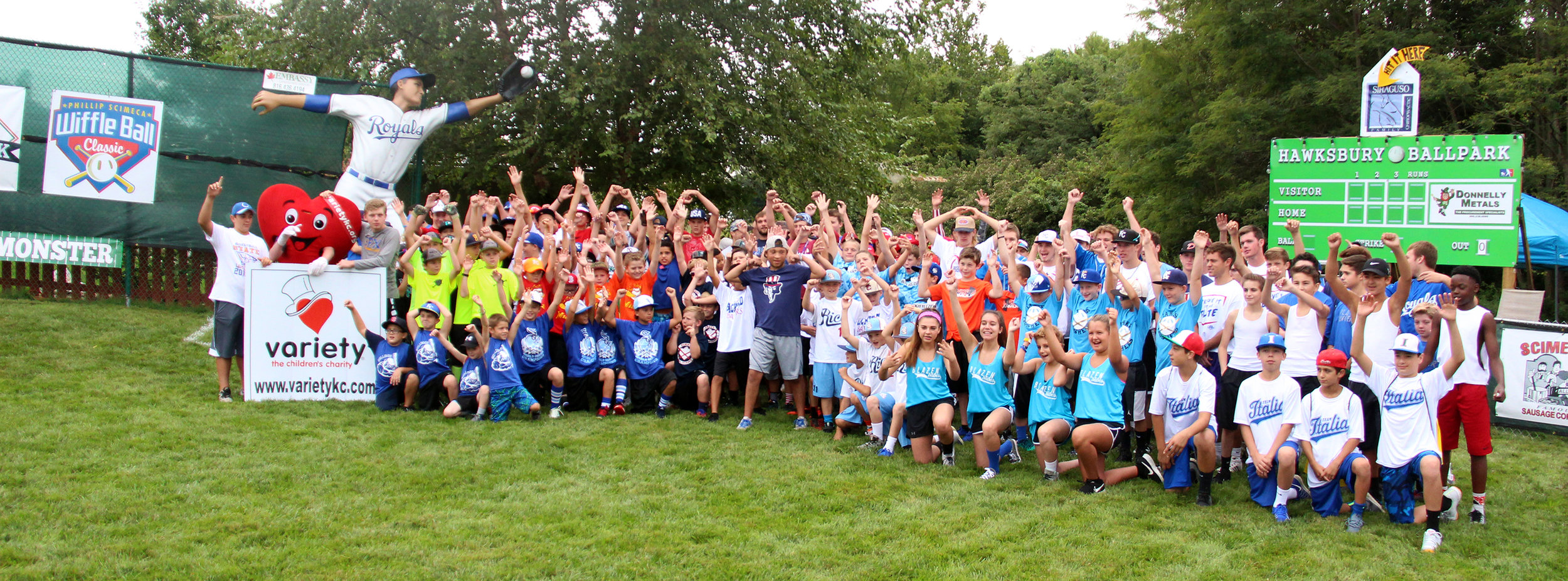 ROSS MARTIN/Citizen photo  Phillip Scimeca (center, standing in a dark blue shirt) poses with a photo of all the participants in the sixth annual Phillip Scimeca Wiffle Ball Classic, held Sunday, Sept. 4 in his neighborhood in Kansas City, Mo. Scimeca, a senior at Platte County, started the event in 2011 in an effort to raise money for victims of the Joplin tornado, and the tournament has grown each year.