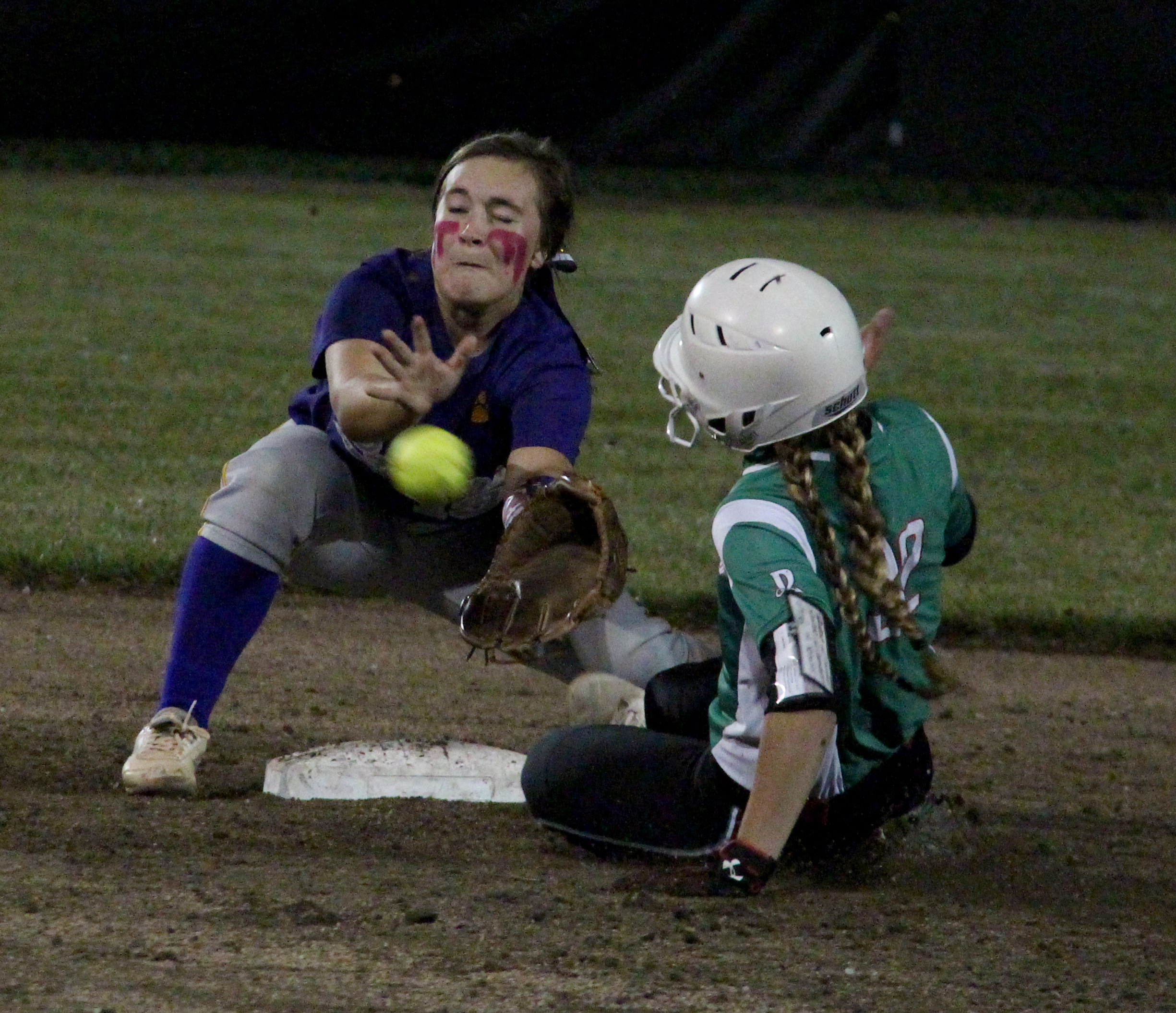ROSS MARTIN/Citizen photo North Platte junior shortstop Alley Rickel, left, fields a throw from catcher Kyra Patch (not pictured) trying to catch Mid-Buchanan's Jill Rumpf stealing during a Class 2 District 14 first-round game Wednesday, Oct. 5 at Lathrop High School in Lathrop, Mo.