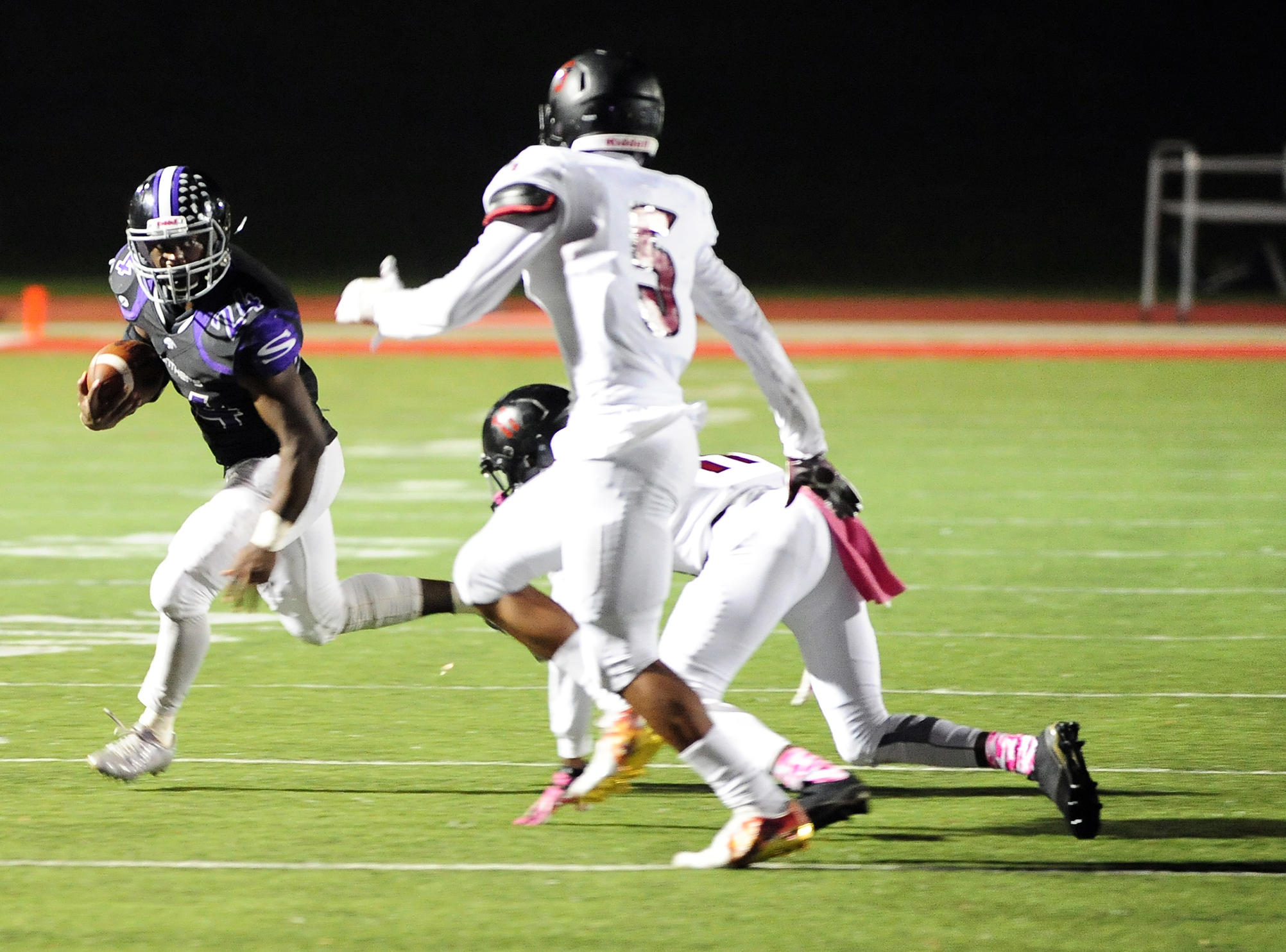 NICK INGRAM/Citizen photo Park Hill South senior running back Emanuel Butler, left, sizes up a pair of Lee's Summit North defenders during a game Friday, Oct. 7 at Park Hill District Stadium in Kansas City, Mo. Park Hill South won 40-26.