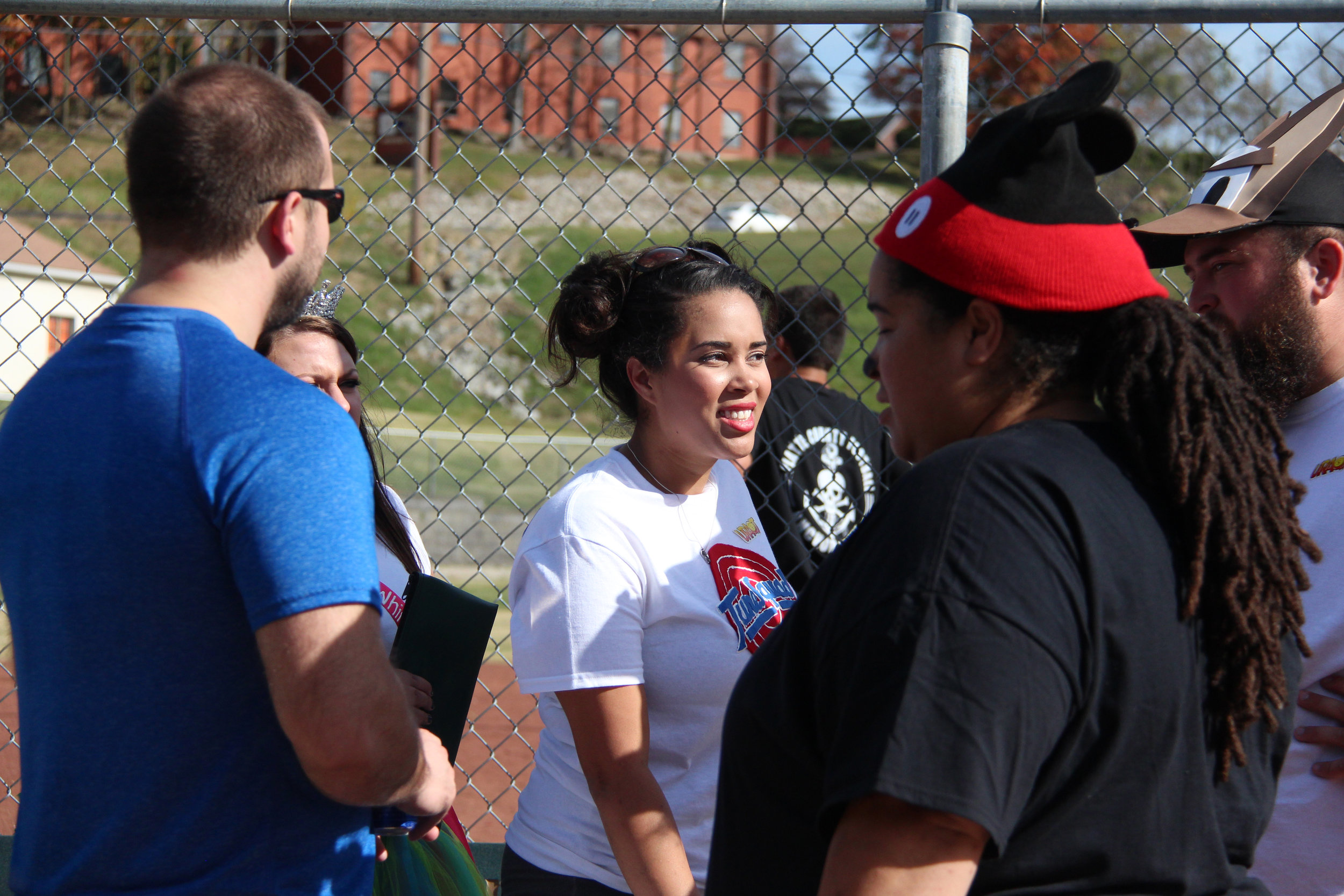 ROSS MARTIN/Citizen photo Alyssa Hon, center, talks with friends and family during a costume kickball tournament they organized. Dozens turned out Saturday, Oct. 29 to Harrel Ferrel Park in Platte City with proceeds from the event donated to the Jaros family.