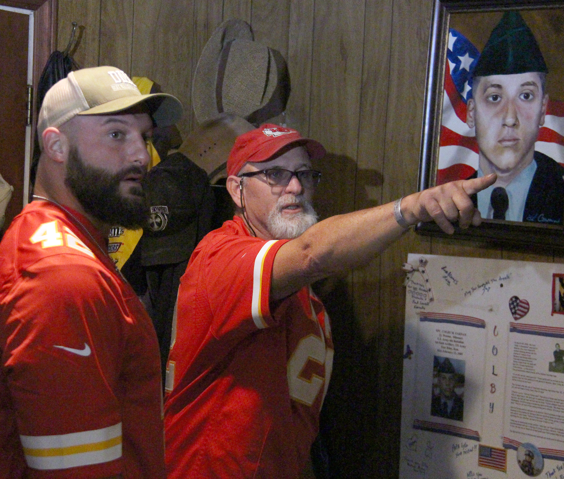 ROSS MARTIN/Citizen photo Patrick Farnan, right, points out a picture to Kansas City Chiefs fullback Anthony Sherman in the basement of the Farnans' home in Weston, Mo. Sherman visited the family Monday, Nov. 7 to present a special pregame-worn hooded sweatshirt he wore prior to a game with the Jacksonville Jaguars a day earlier. The shirt bore the name of SPC Colby Farnan, shown in the background of this photo in a portrait on the wall. He was killed in 2005 while serving in the United States Army.