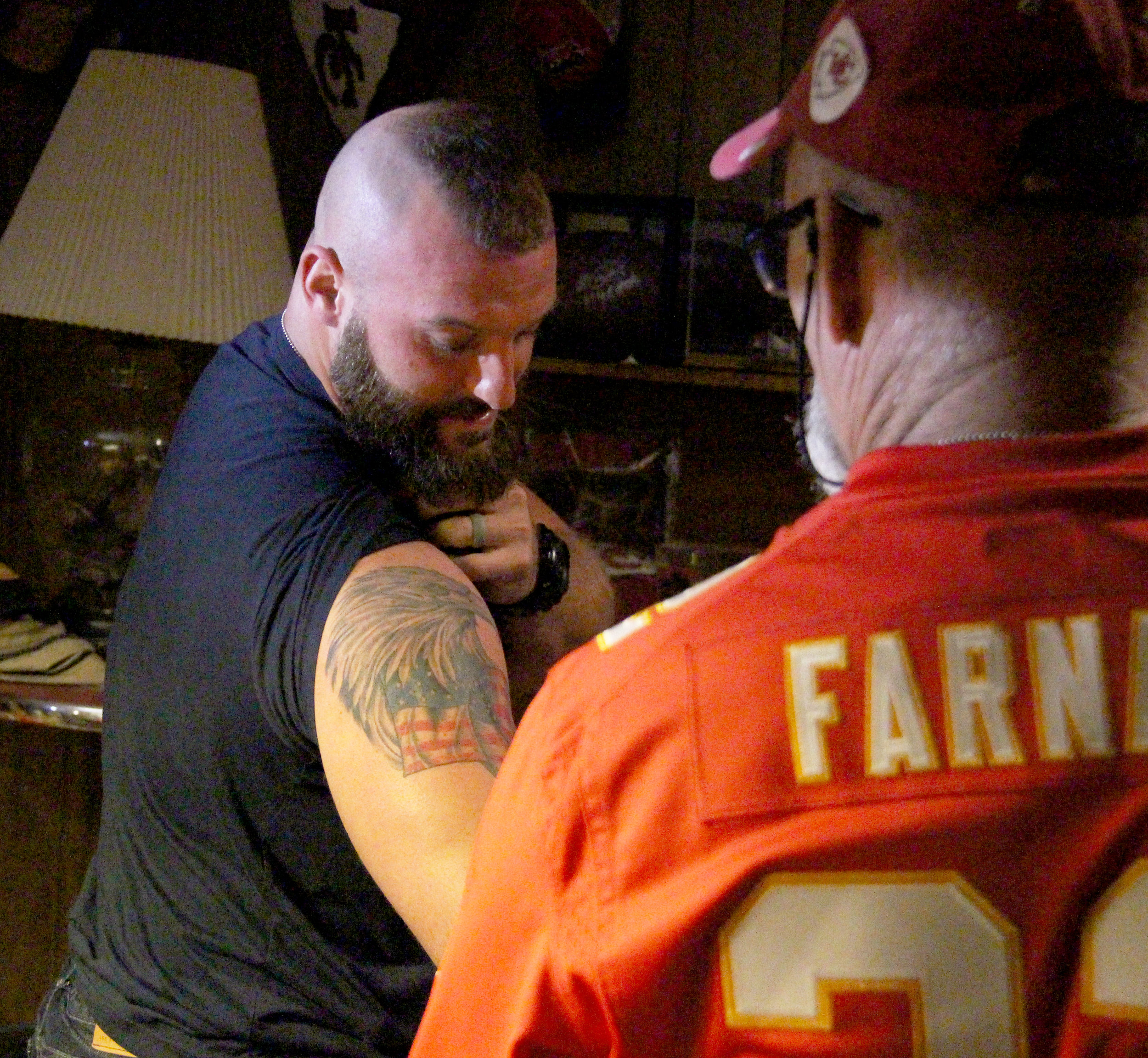 ROSS MARTIN/Citizen photo Patrick Farnan, front, marvels at an American themed tattoo on the arm of Kansas City Chiefs fullback Anthony Sherman.