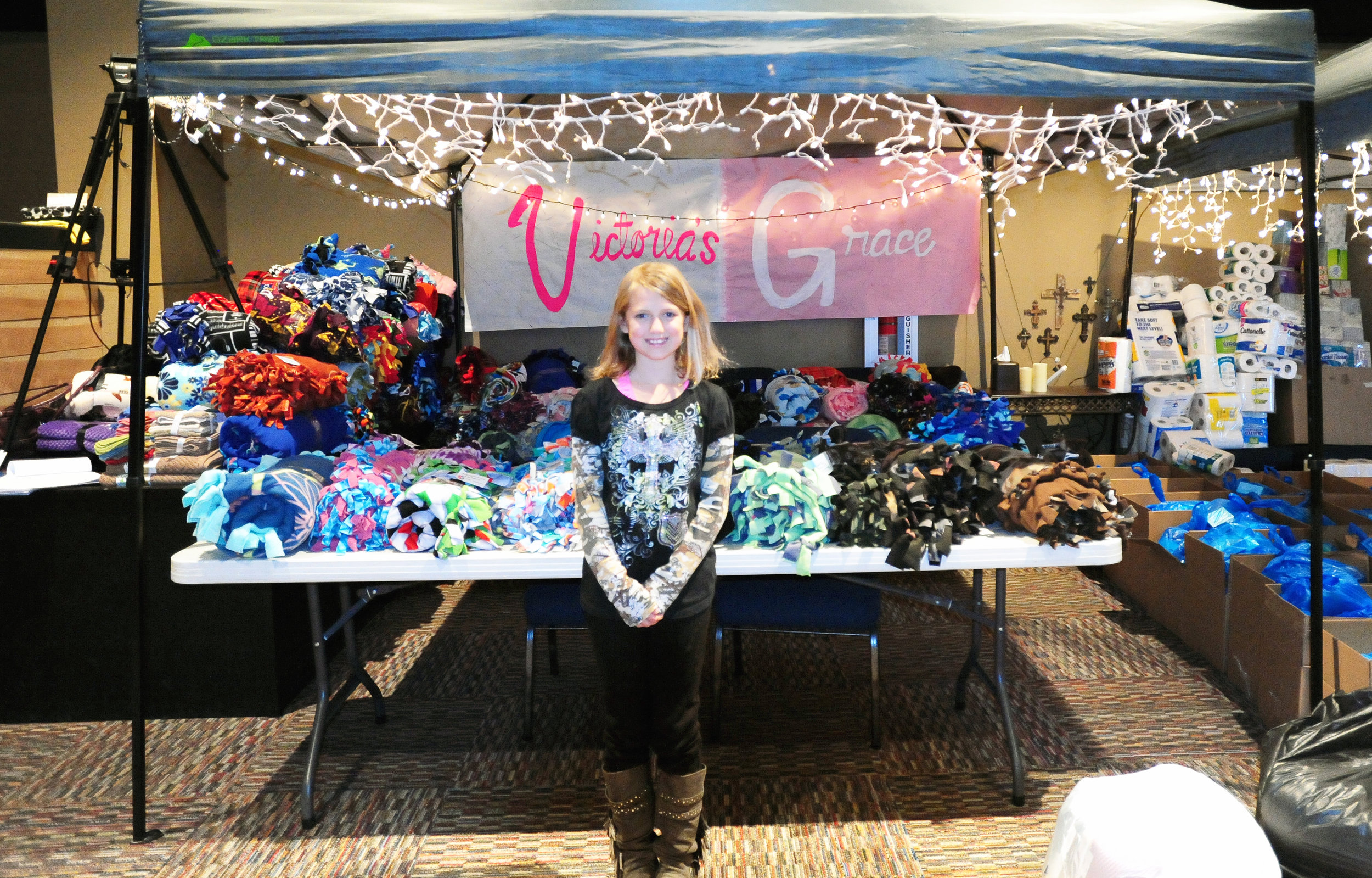 NICK INGRAM/Citizen photo Victoria Robinson stands in front of her booth with her sign created by students in the Platte County High School art class. Robinson was able to collect nearly 90 blankets and handed them out to families in need.