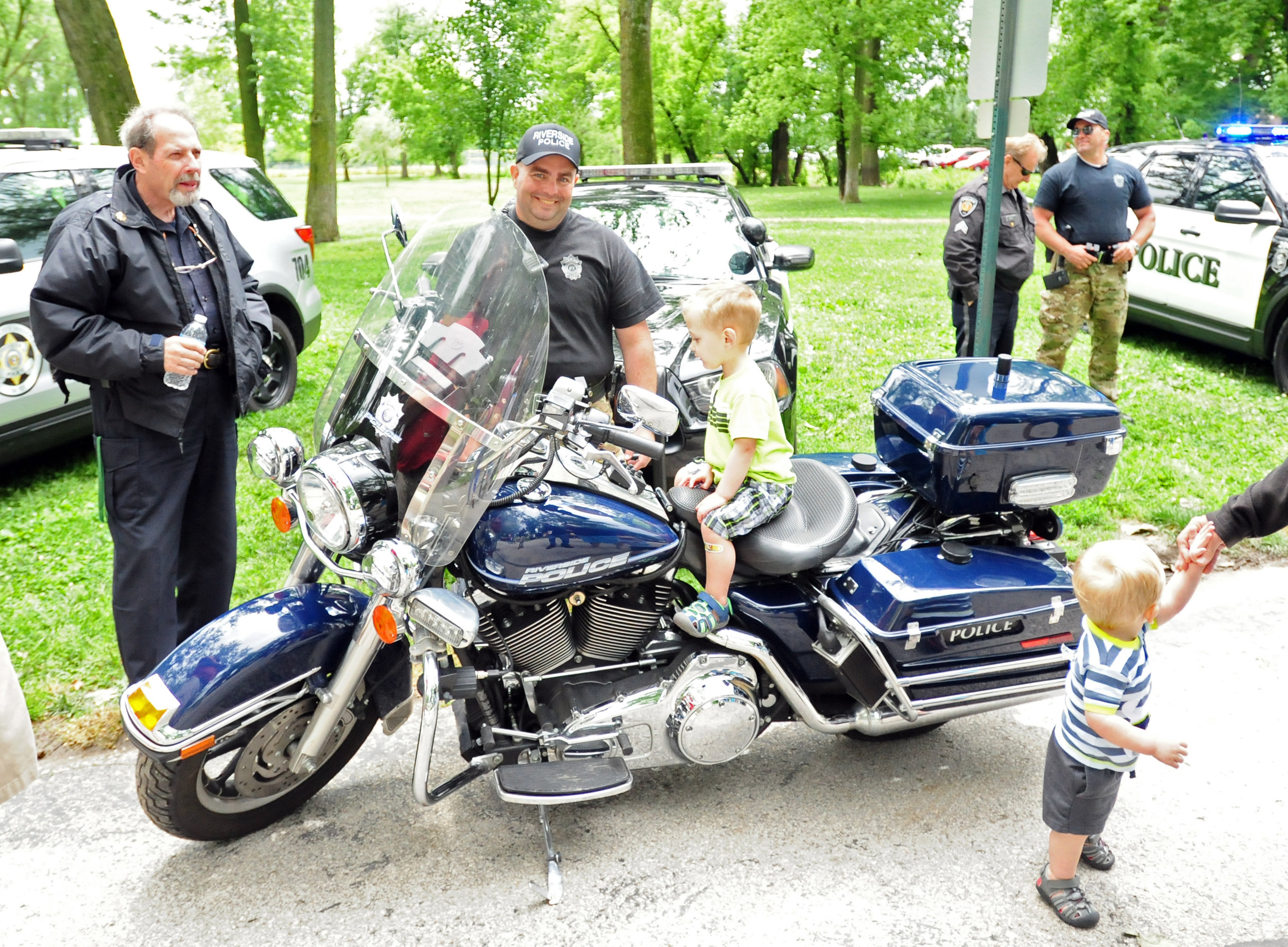 NICK INGRAM/Citizen photo Officer Josh Collins (center) of the Riverside (Mo.) Police Department stands by Blake Baldwin, 3, from Kansas City, Mo. as he sits on one of the department's motorcycles at the Northland Law Enforcement Appreciation Day on Saturday, May 20 at English Landing Park in Parkville, Mo.