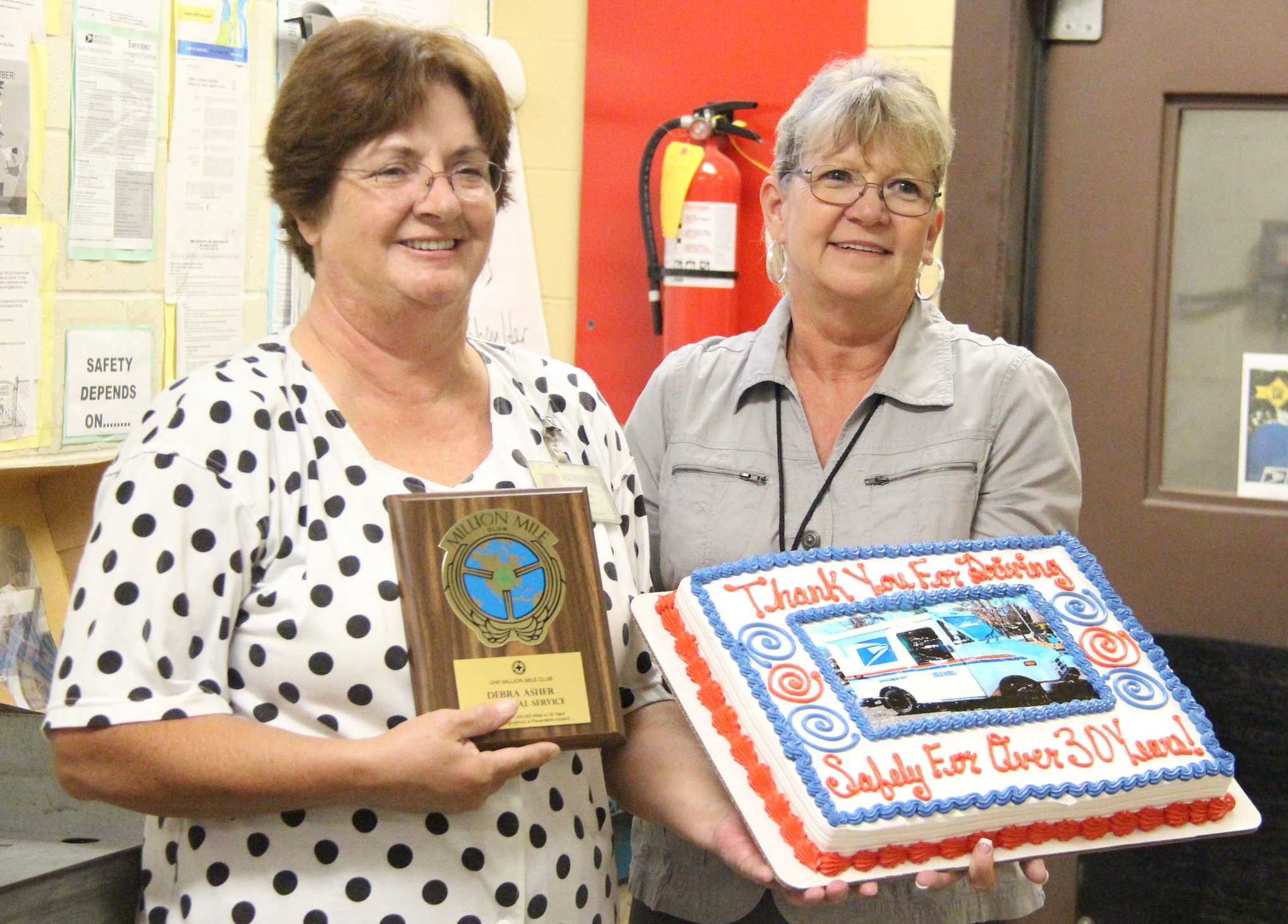 """ROSS MARTIN/Citizen photo Platte City Post Office postmaster Marla Eschbacher, right, presented long time mail carrier Debbie Asher with a National Safety Council """"Million Mile Award"""" for her service. Asher has spent 34 years as a carrier in Platte City, including 26 in a full-time capacity. The award goes to workers who have logged one million miles of driving or at least 30 years with driving as a daily duty with no accidents."""