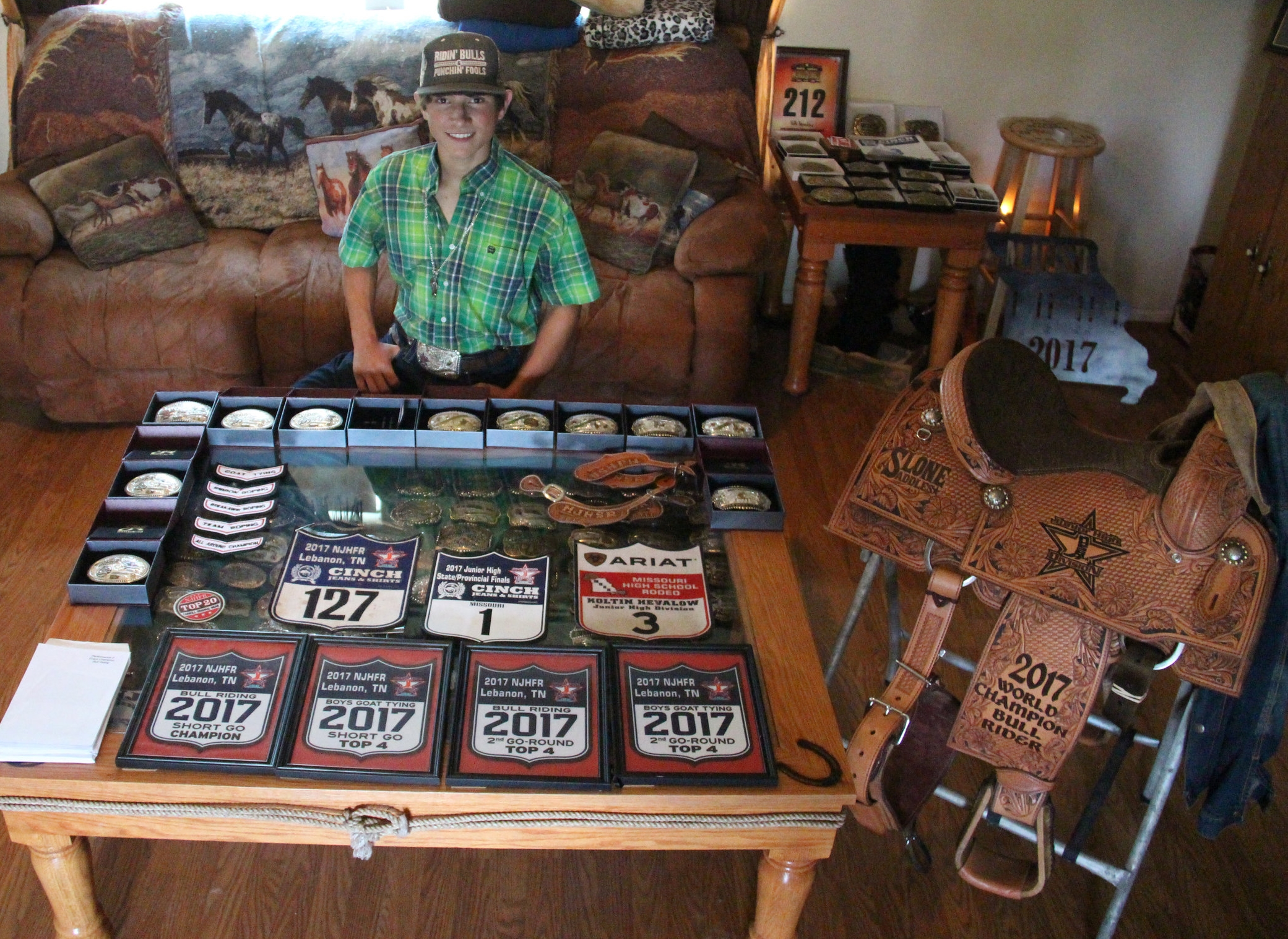 ROSS MARTIN/Citizen photo Koltin Hevalow, who will be a freshman this year at Platte County High School, poses in his living room with his numerous rodeo awards won during his youth career. He recently won a saddle for capturing the National High School Rodeo Association (NHSRA) Junior High Division junior bull riding world championship.