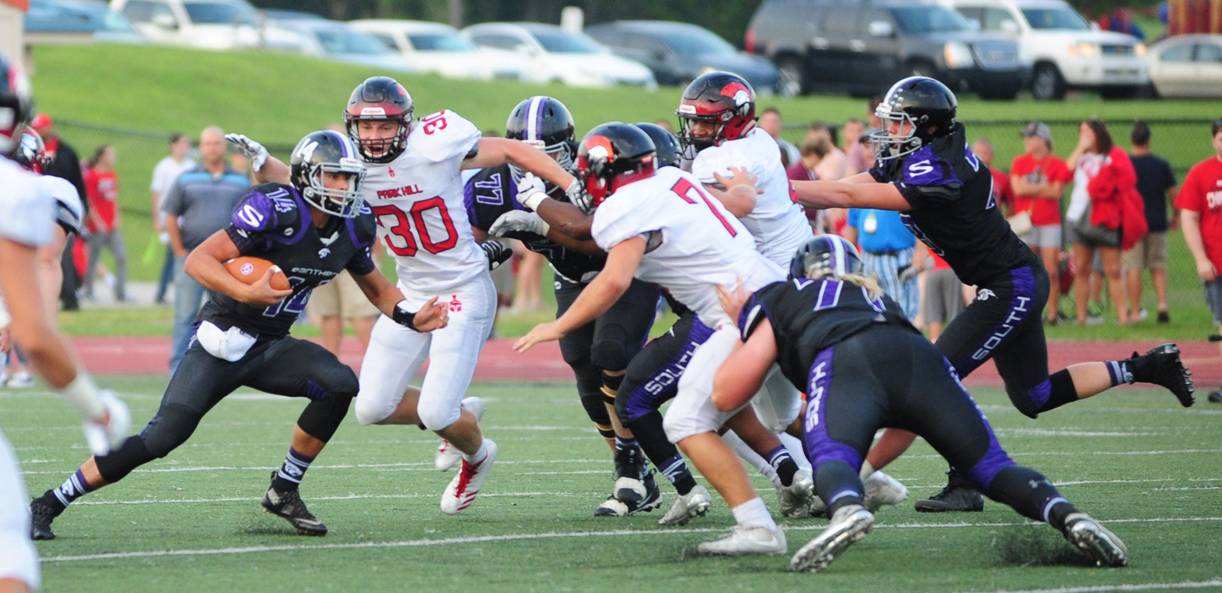 NICK INGRAM/Citizen photo Park Hill linebackers Haden Wallace (30) and Cole Gonier (7) converge trying to stop Park Hill South quarterback Billy Eggers during a game Friday, Sept. 1 at Park Hill District Stadium in Kansas City, Mo.