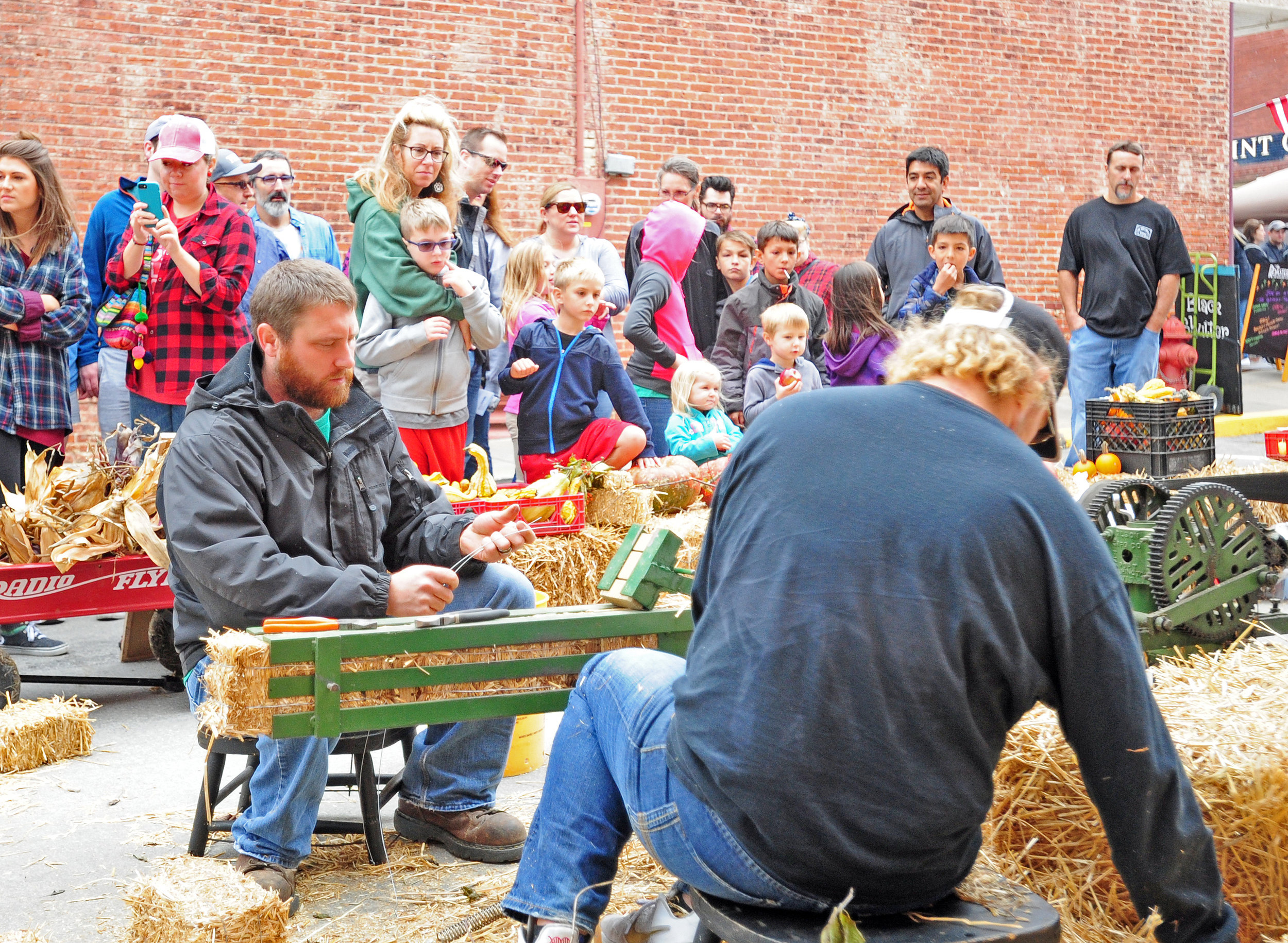 NICK INGRAM/Citizen photo Spectators watch as workers put straw into a machine to make miniature bales of hay during Applefest on Saturday, Oct. 7 in Weston, Mo.