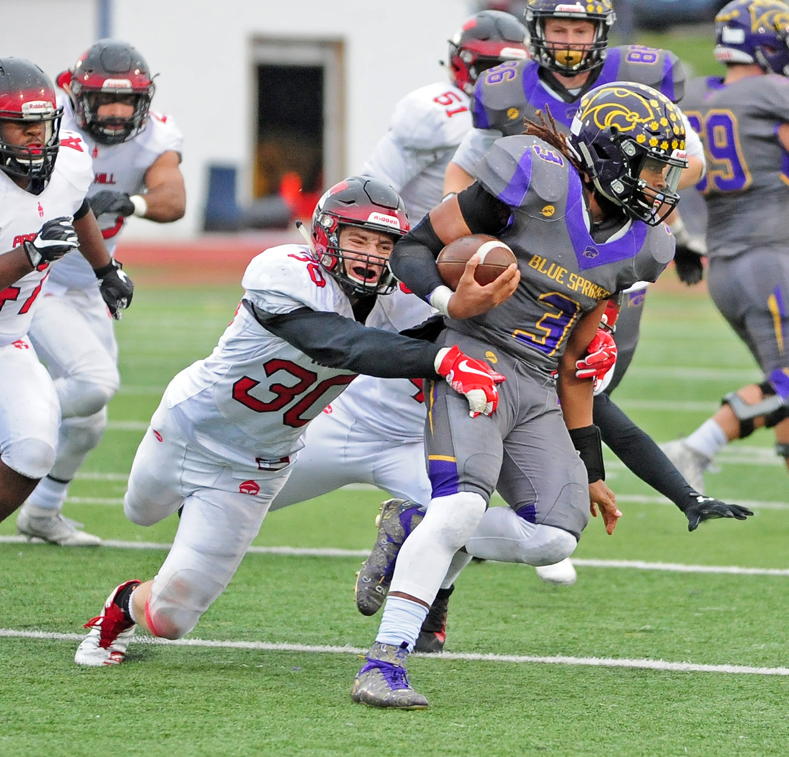 NICK INGRAM/Citizen photo Park Hill junior linebacker Haden Wallace, left, wraps up Blue Springs running back Aveion Bailey during a Class 6 semifinal Saturday, Nov. 11 in Blue Springs, Mo.